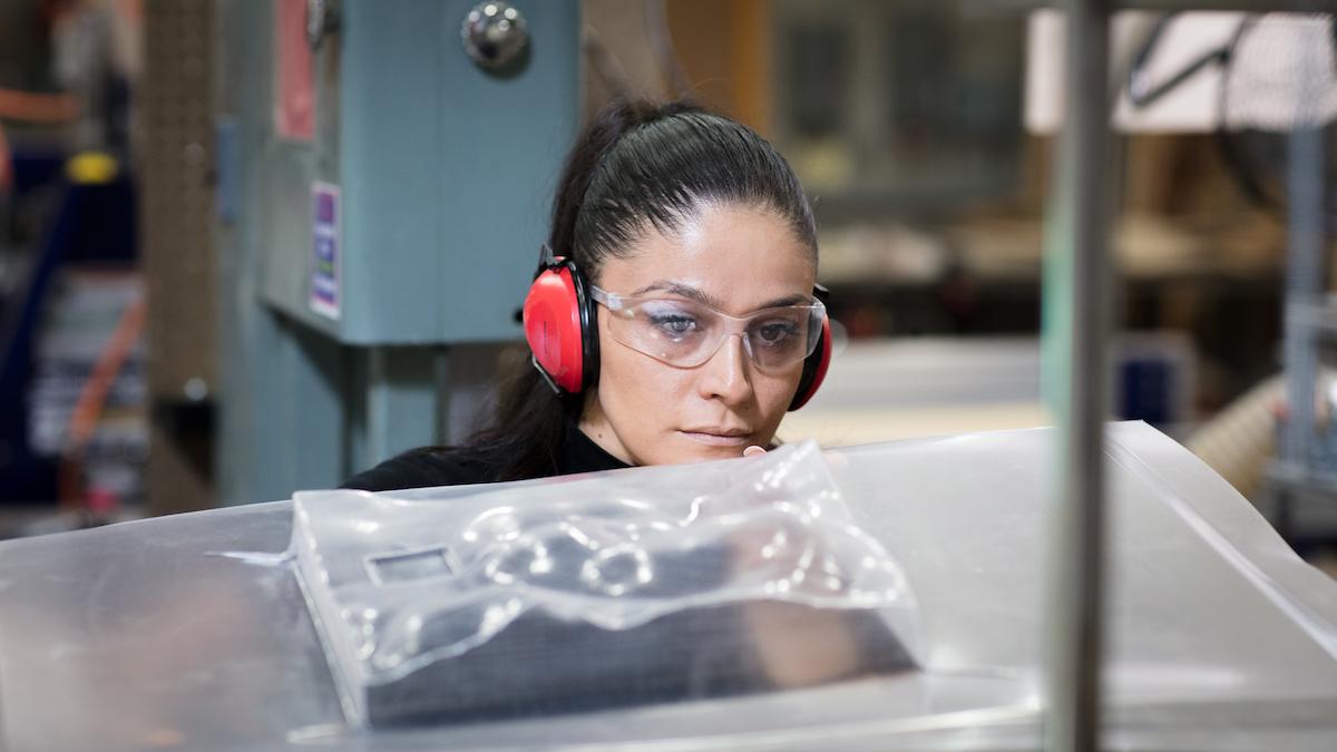 Mona Ghandi working on model in shop.