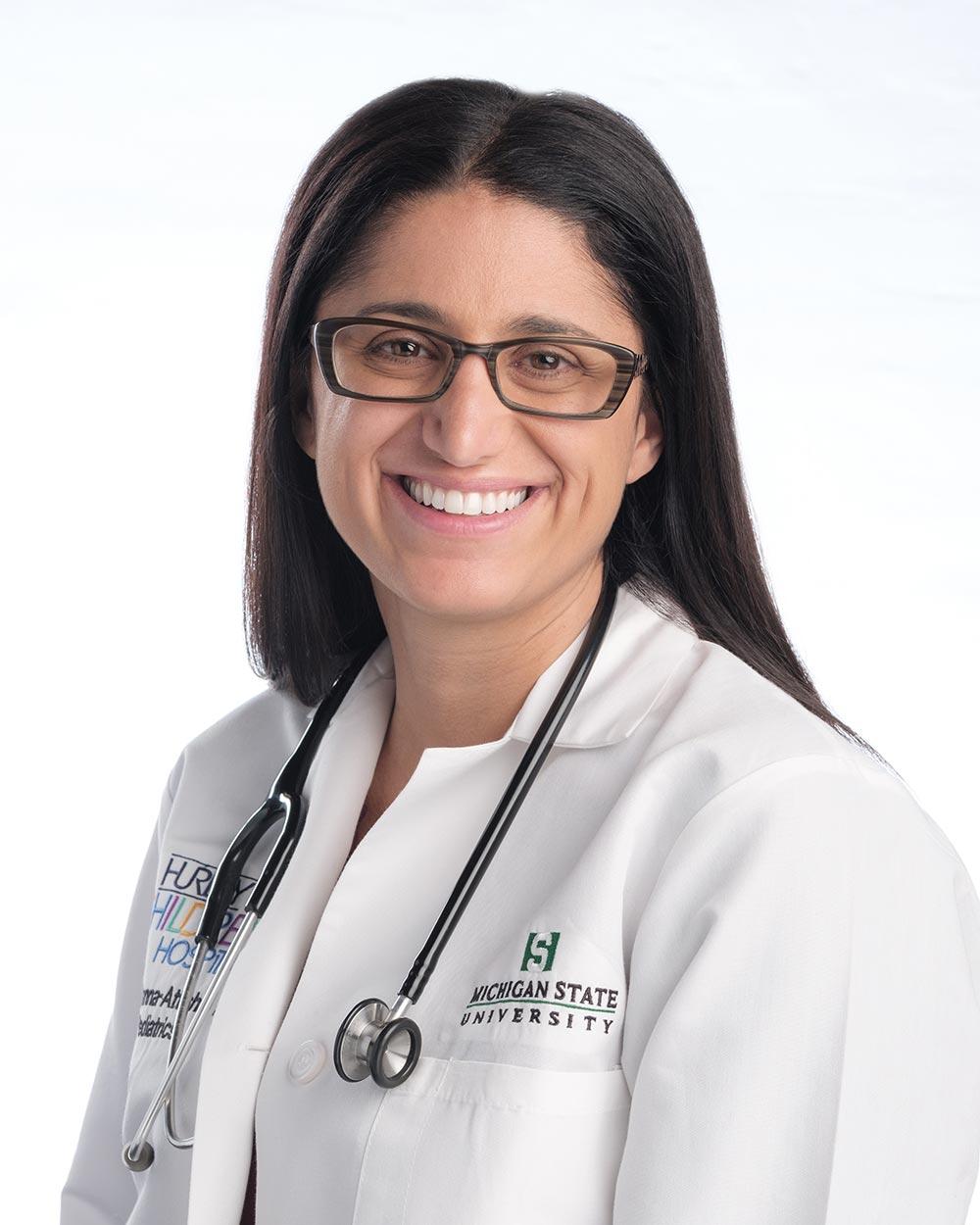 A portrait of Dr. Mona Hanna-Attisha in a lab coat.