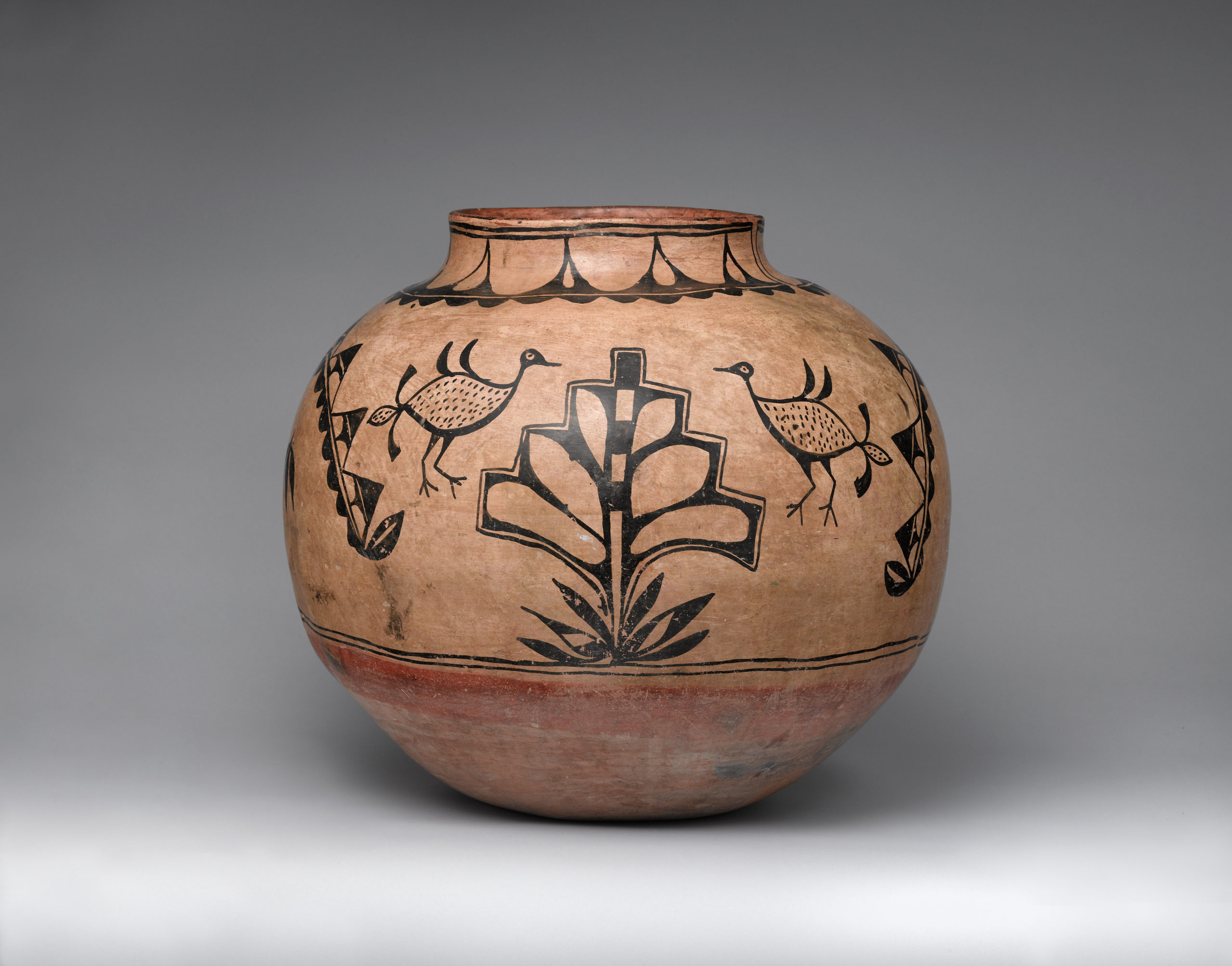 A brown Cochiti jar painted with a black design including leaves, a plant, and four birds.