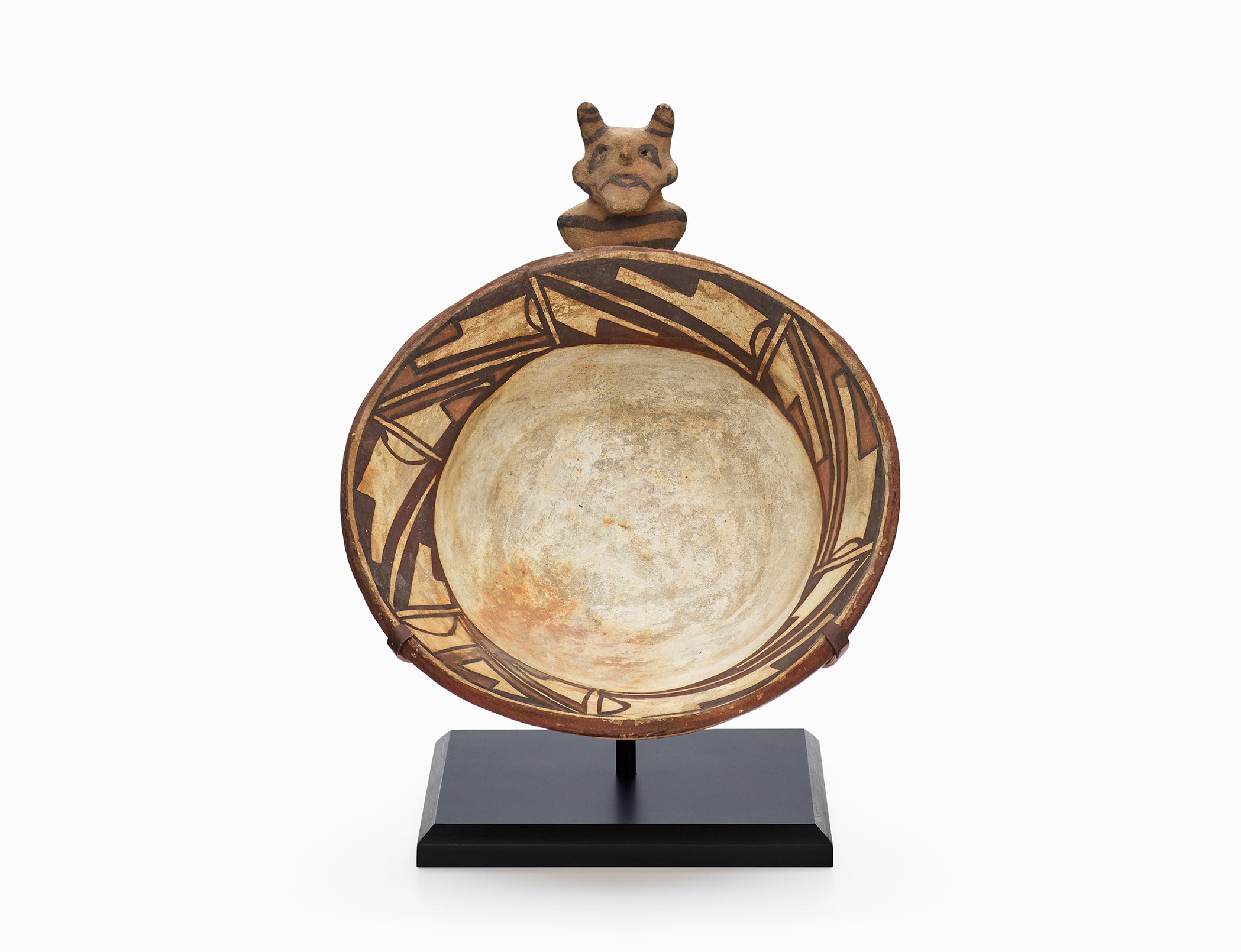 A Hopi bowl with a geometric design around the lip and a sculpted clown figure on the rim.