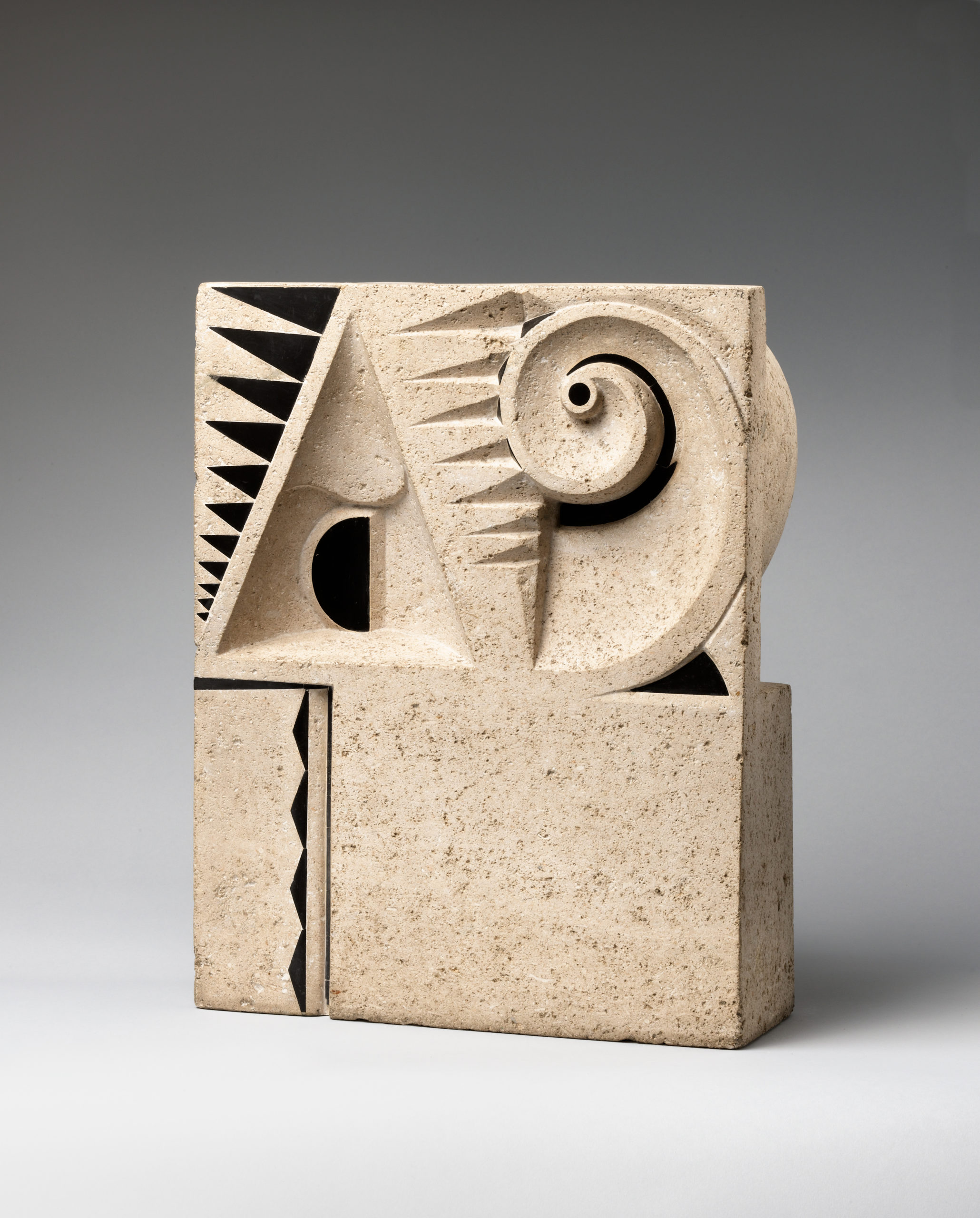 Rectangular limestone block carved with abstractions of geometric shapes, inlay of black stone in triangular patterns, and a spiral that loops at the top-right corner.