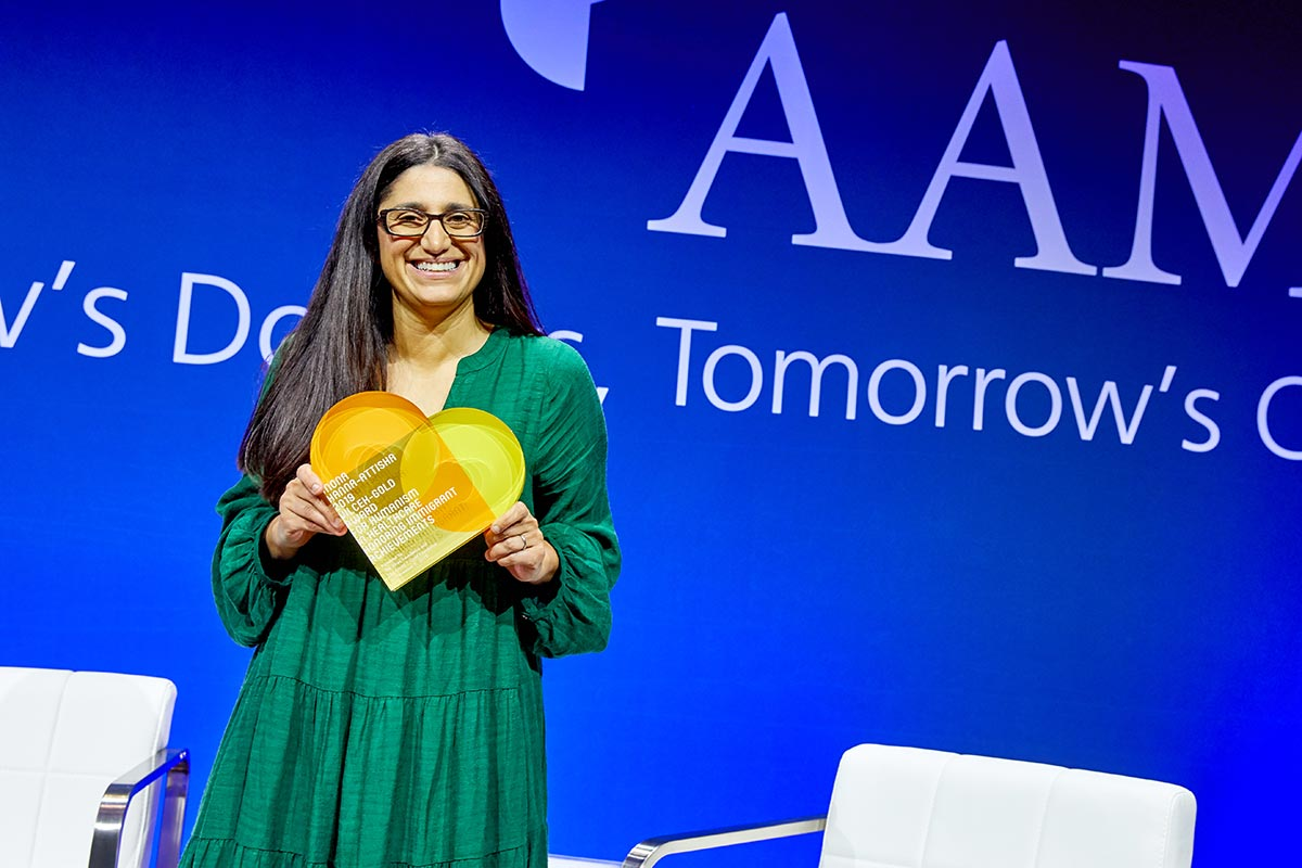 Mona Hanna-Attisha, holding a heart-shaped award, stands on a stage with a blue backdrop of the AAMC.