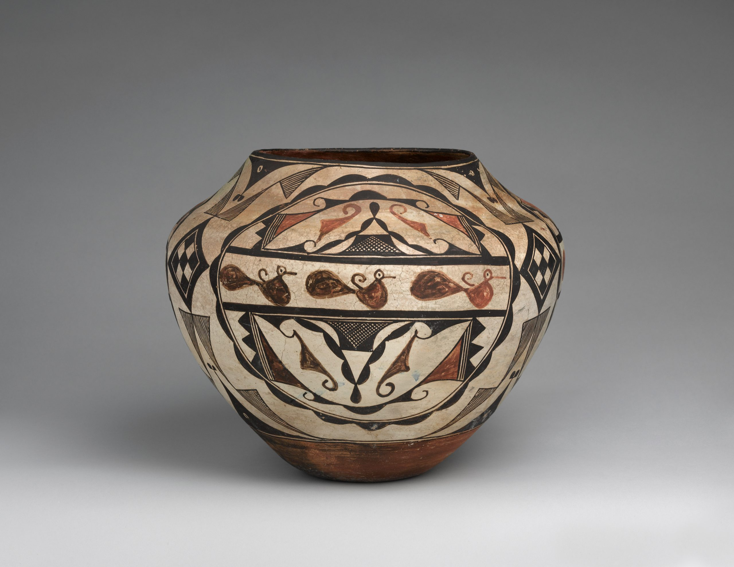 Beige Acoma pot with various geometric shapes and patterns in brown and black, and a row of three identical animals in the center.