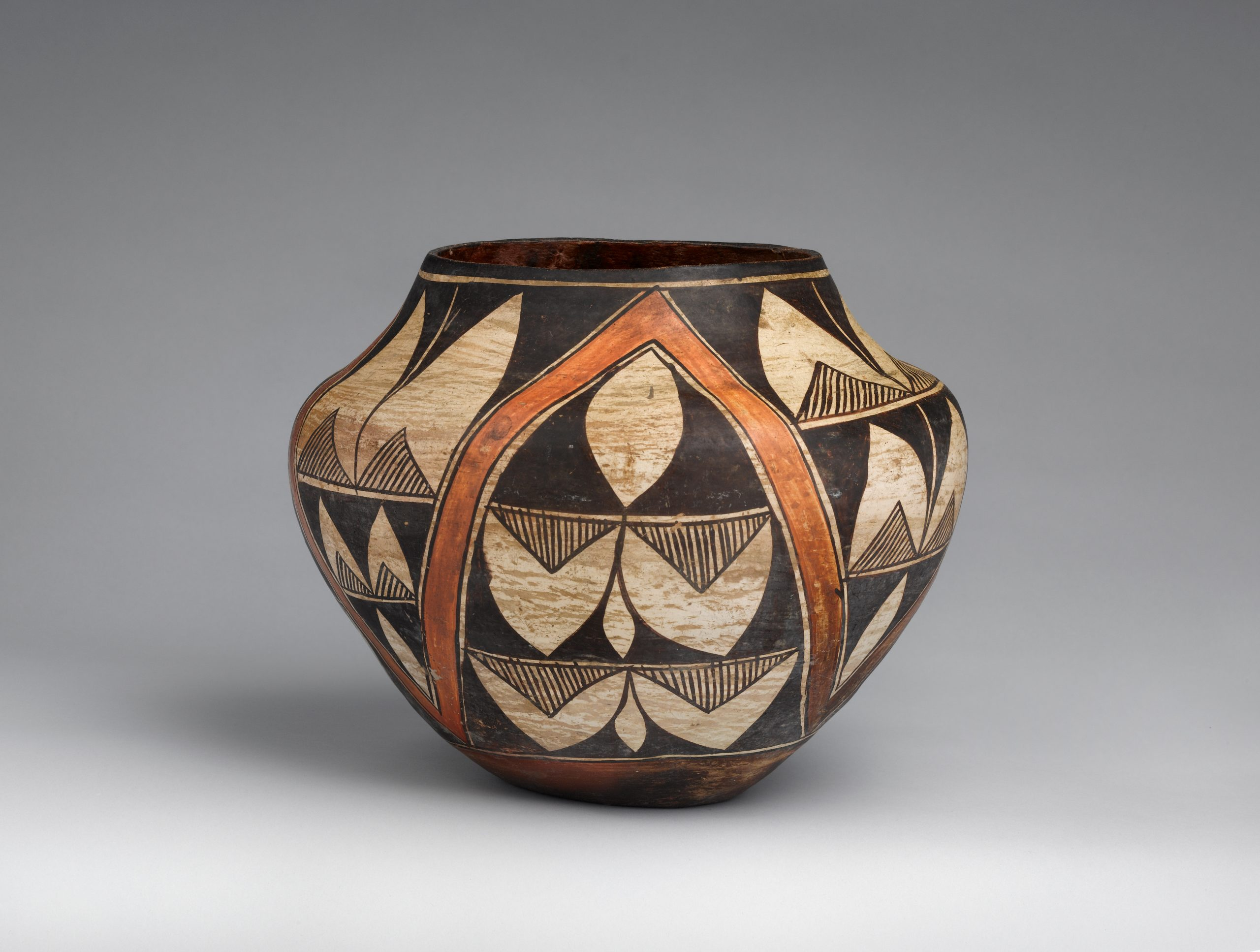 Large white vessel decorated with gray geometric patterns with indentations for holding.
