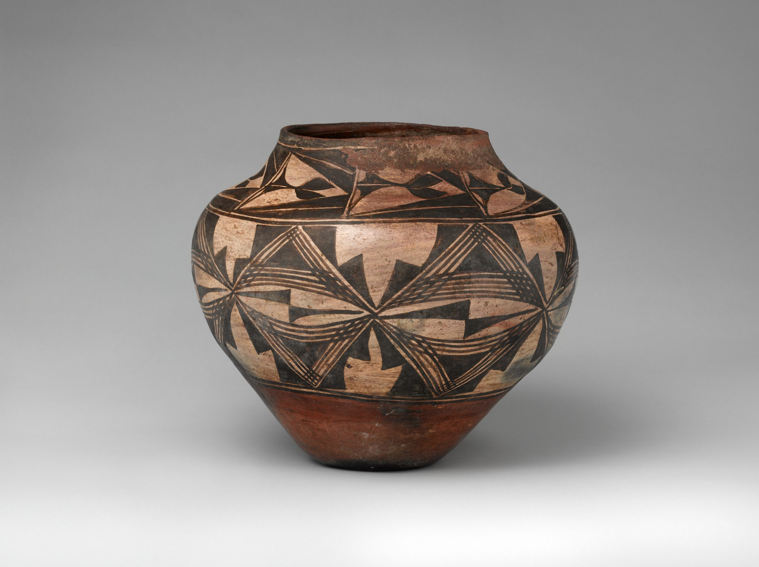 A Zia pot painted brown, black, and beige, with two bands of geometric designs.