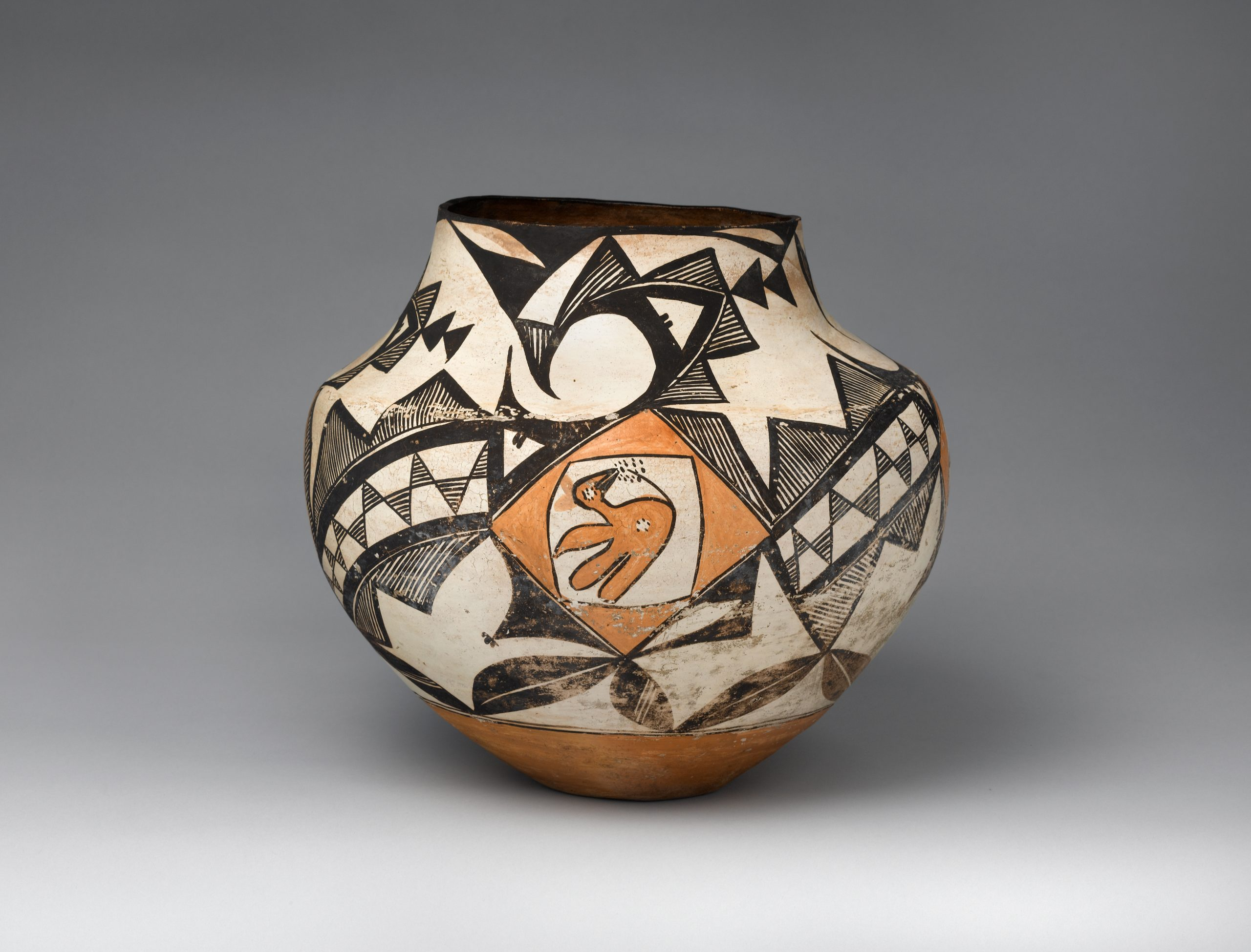 An Acoma jar decorated with a yellow bird and abstract geometric shapes and lines in black, white, and yellow.