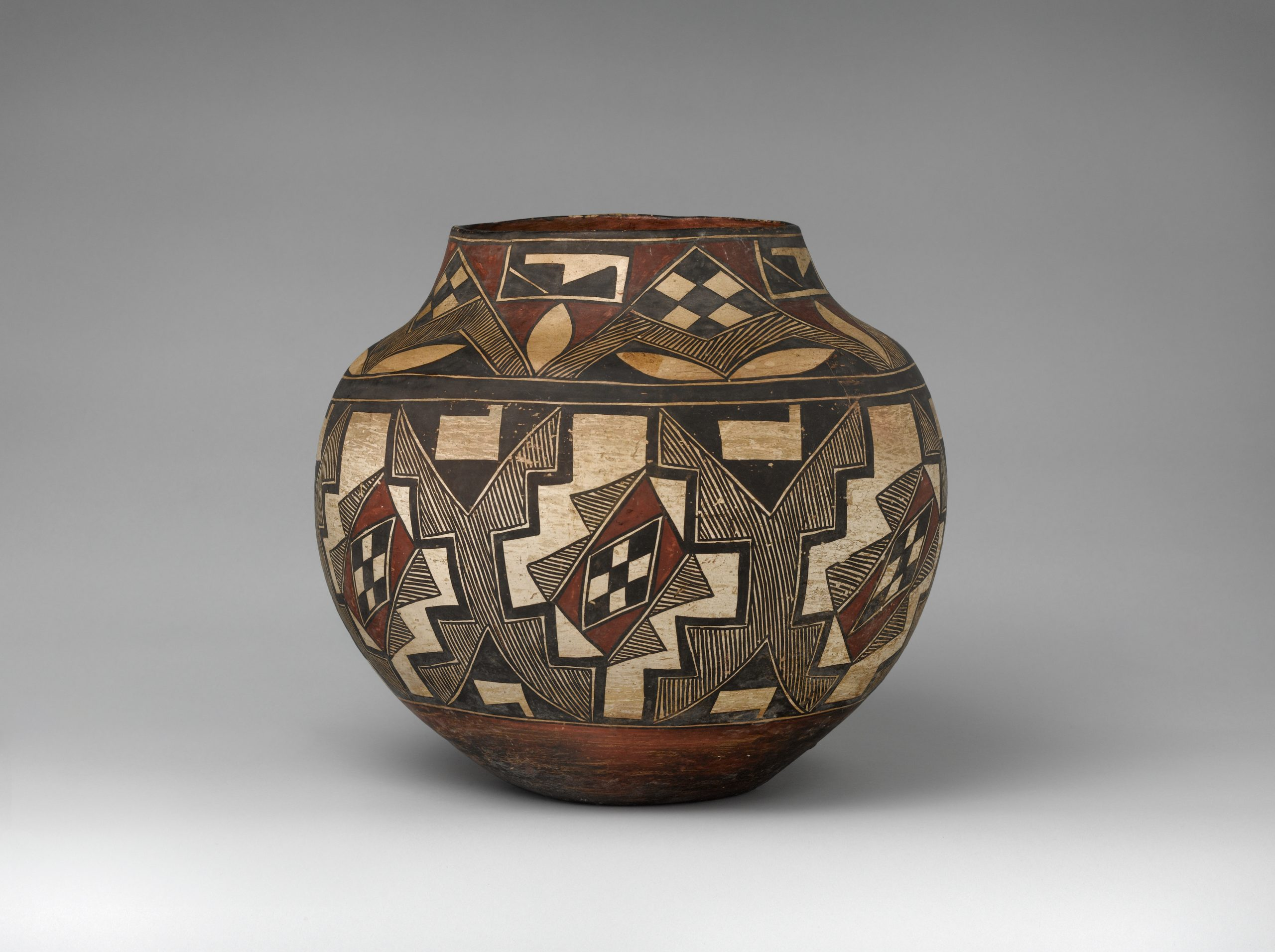 An Acoma jar with two bands of checkered, linear, and geometric patterns in black, beige, and rust-brown pigments.
