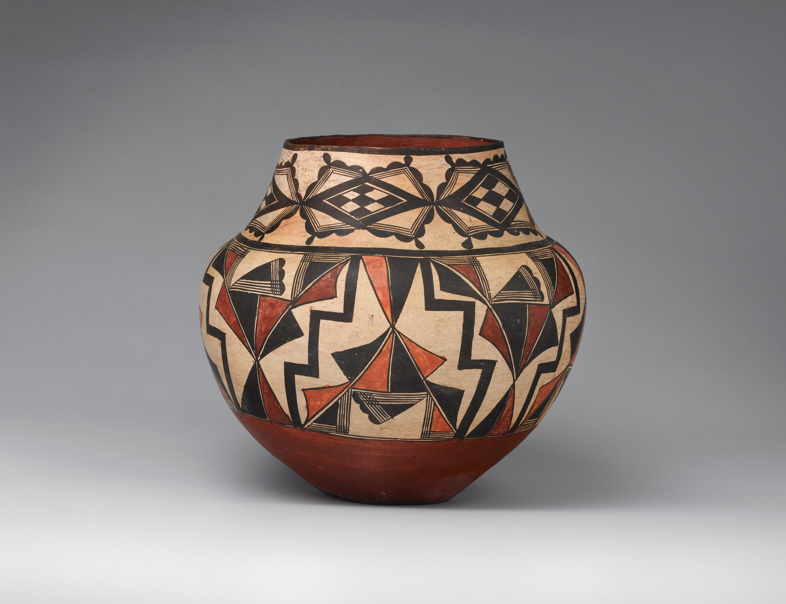 An Acoma jar decorated with black, beige, rust-brown, and red geometric patterns.