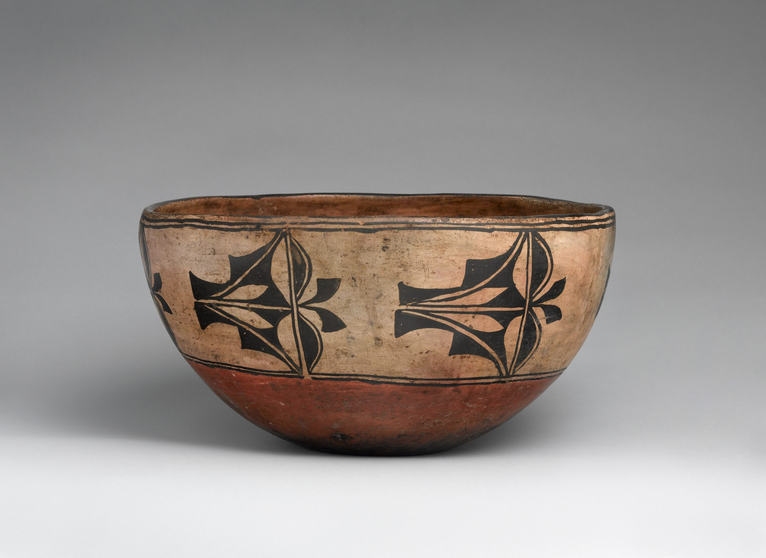 Clay pottery bowl with red rim and circular decorative shapes.