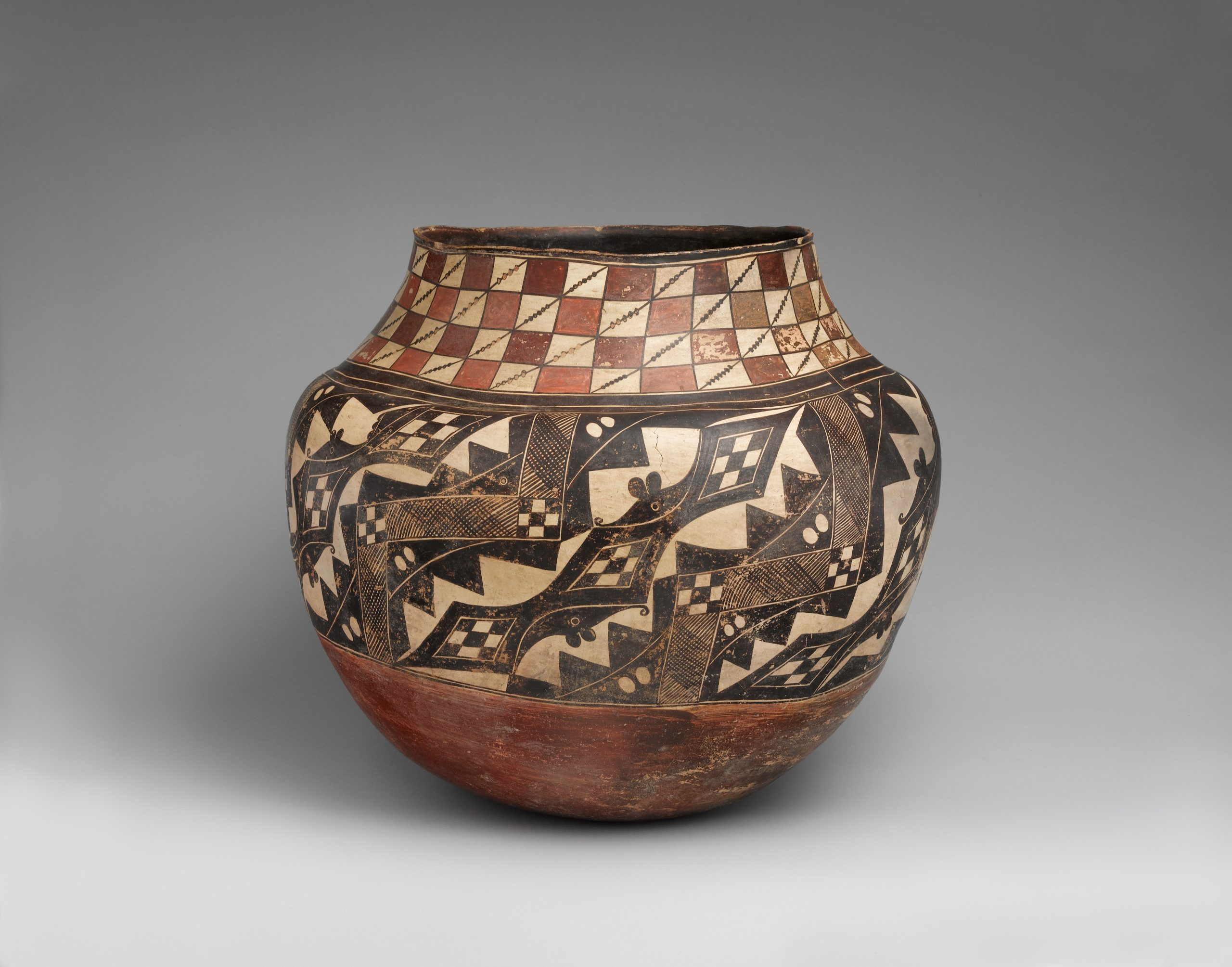 An Acoma olla with a brown and beige checkboard pattern atop a black and beige geometric design.