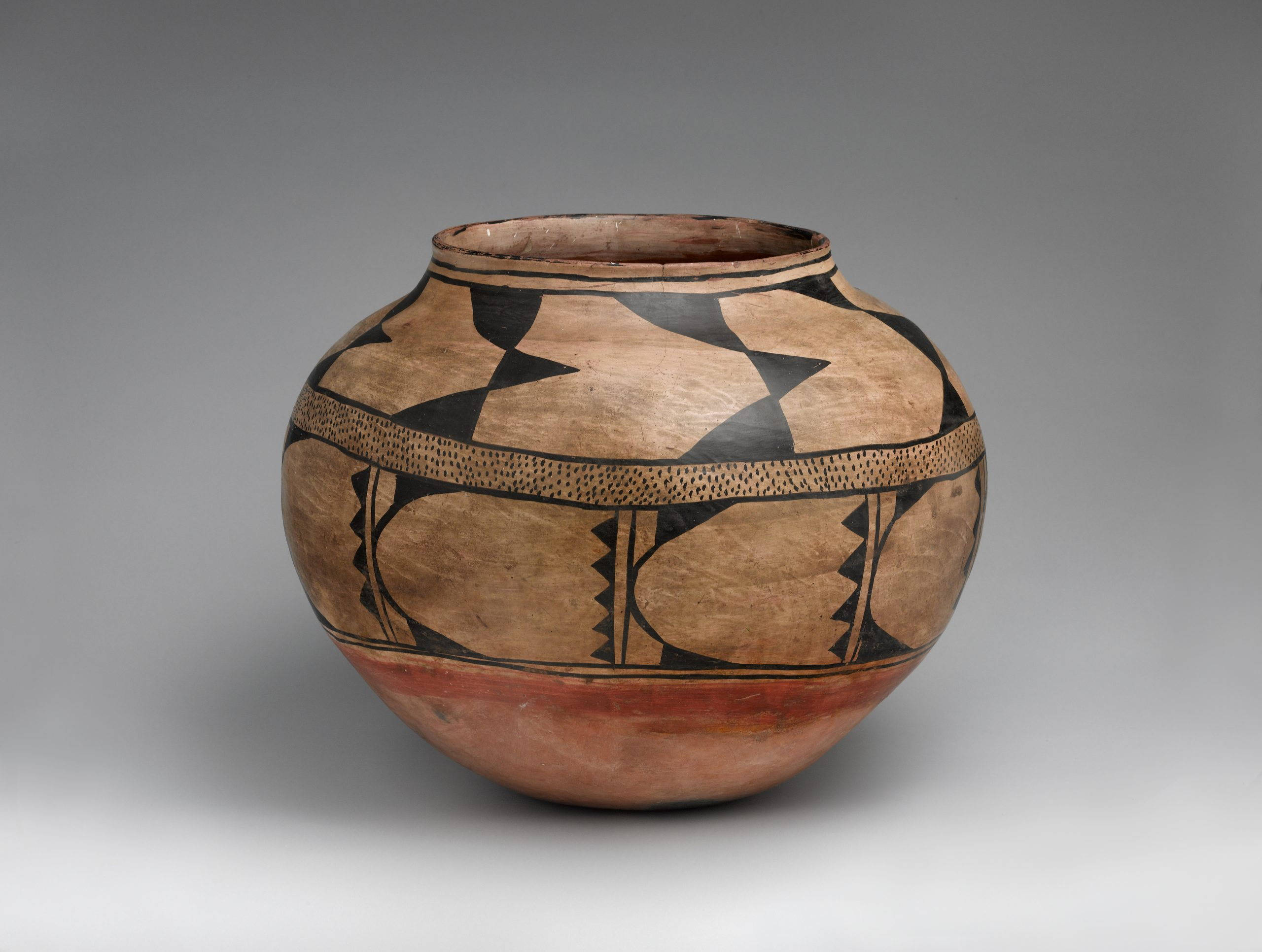 Acoma jar painted beige, rust orange, and black, with an abstract bird design.