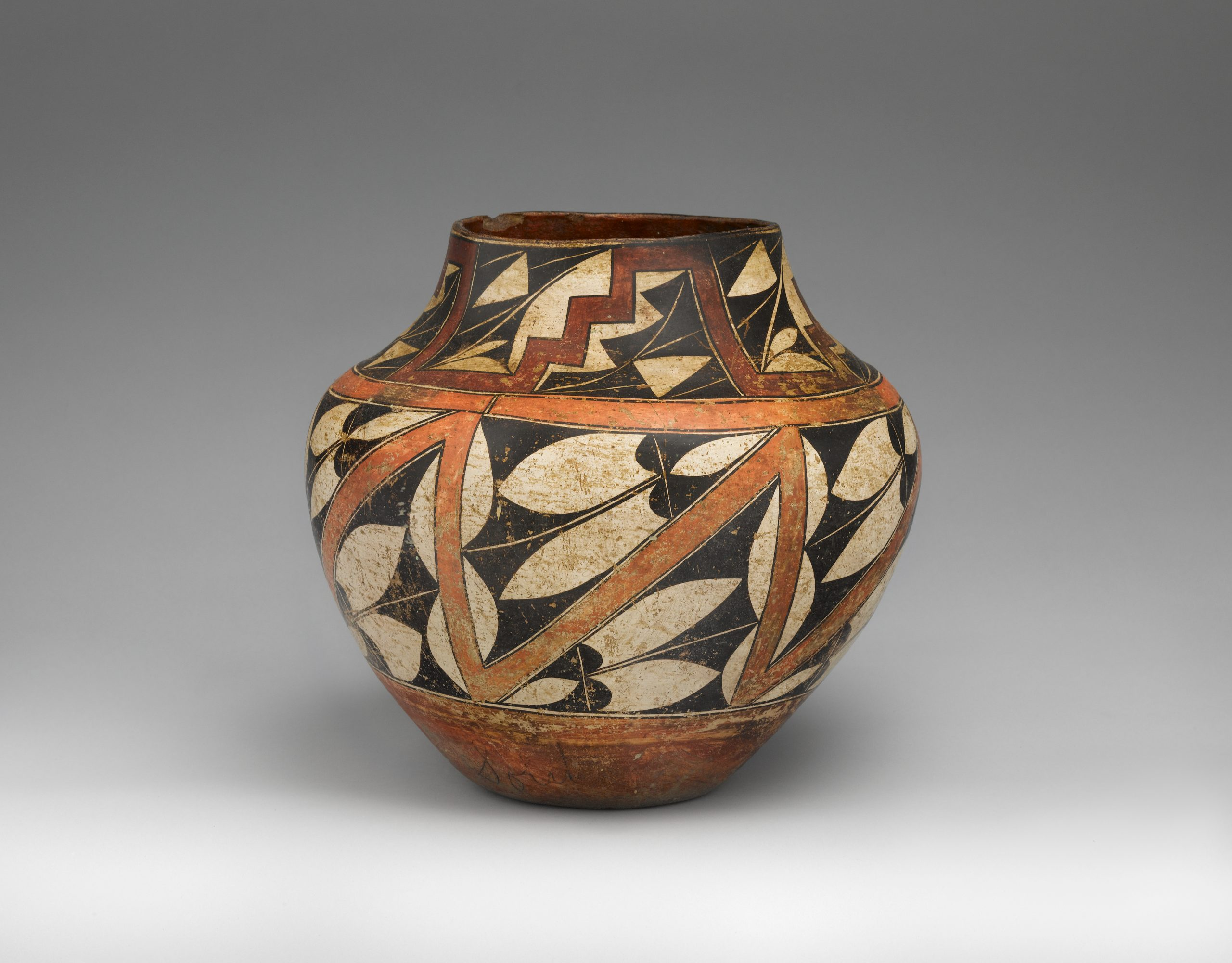 An Acoma pot decorated in white, red, orange, and black geometric shapes.