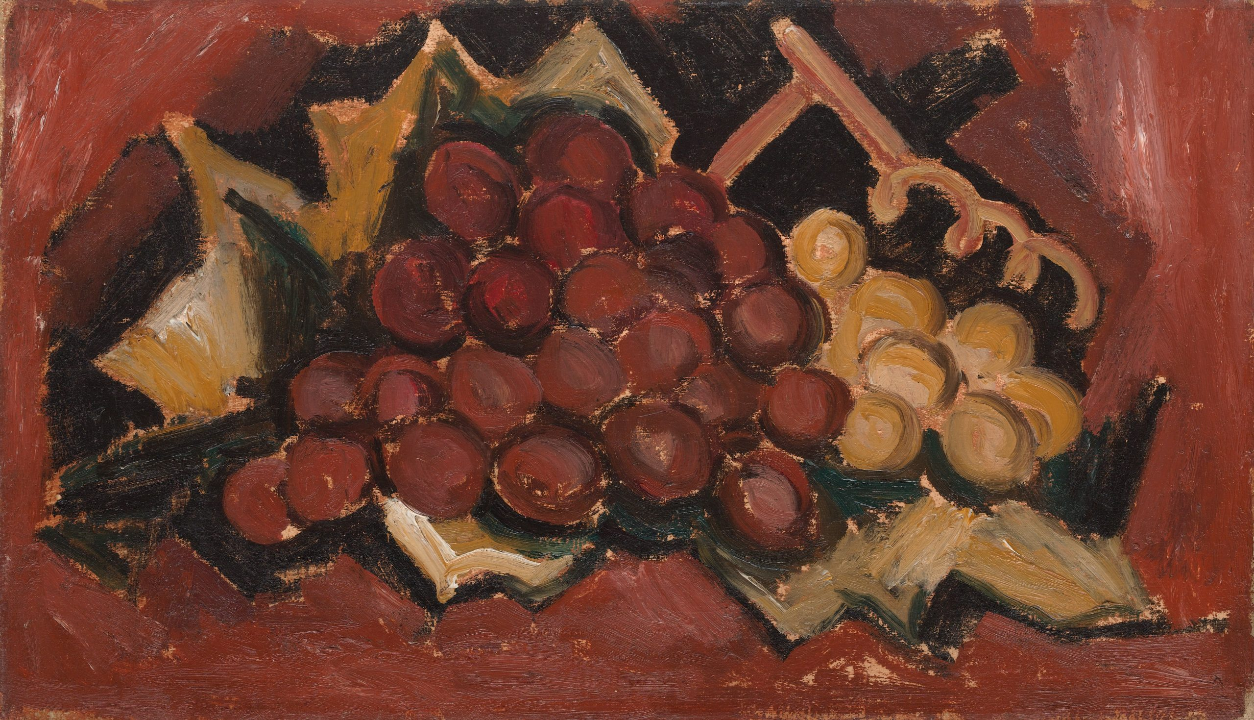 A bunch of red and yellow grapes wrapped in brown paper set against a deep red background.