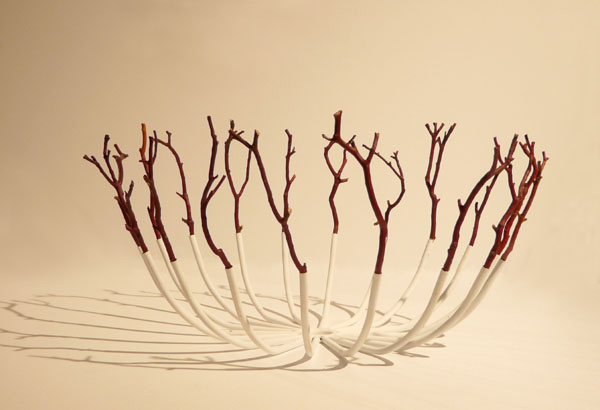An off-white bowl made of steel prongs and dark red twigs.