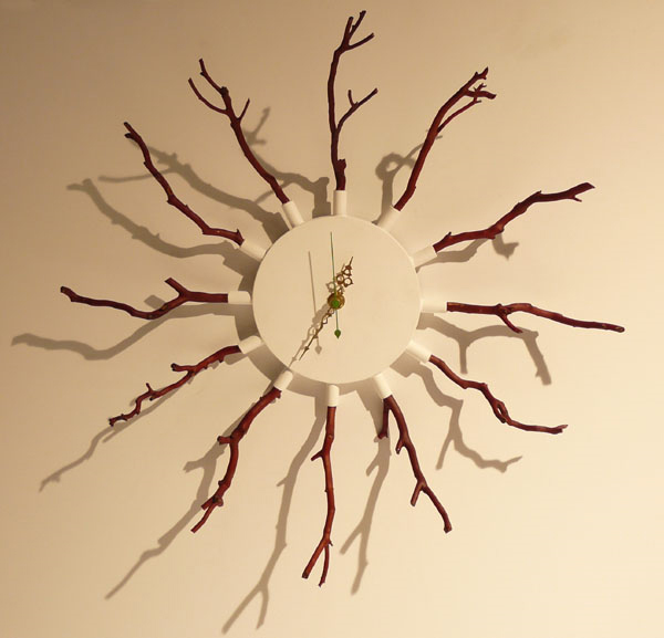 An off-white wall clock with dark red twigs depicting the hours with two gold ornate clock hands.