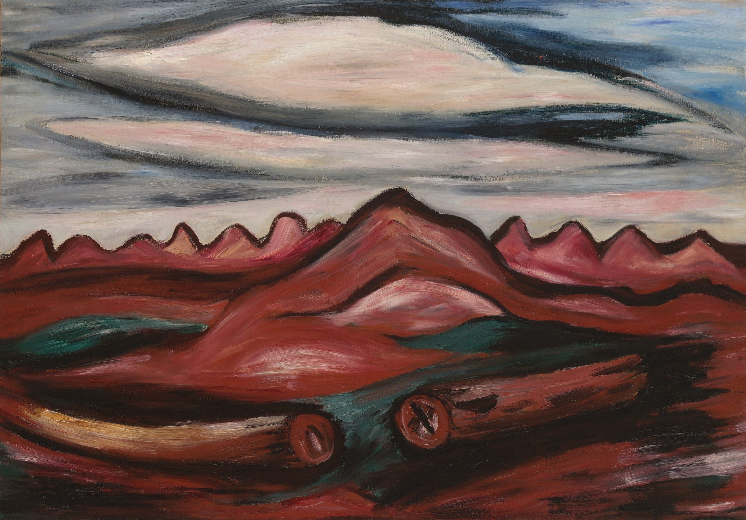 Landscape of red hills under a cloudy sky. A large hill at the center with two fallen logs lying on the ground in front.