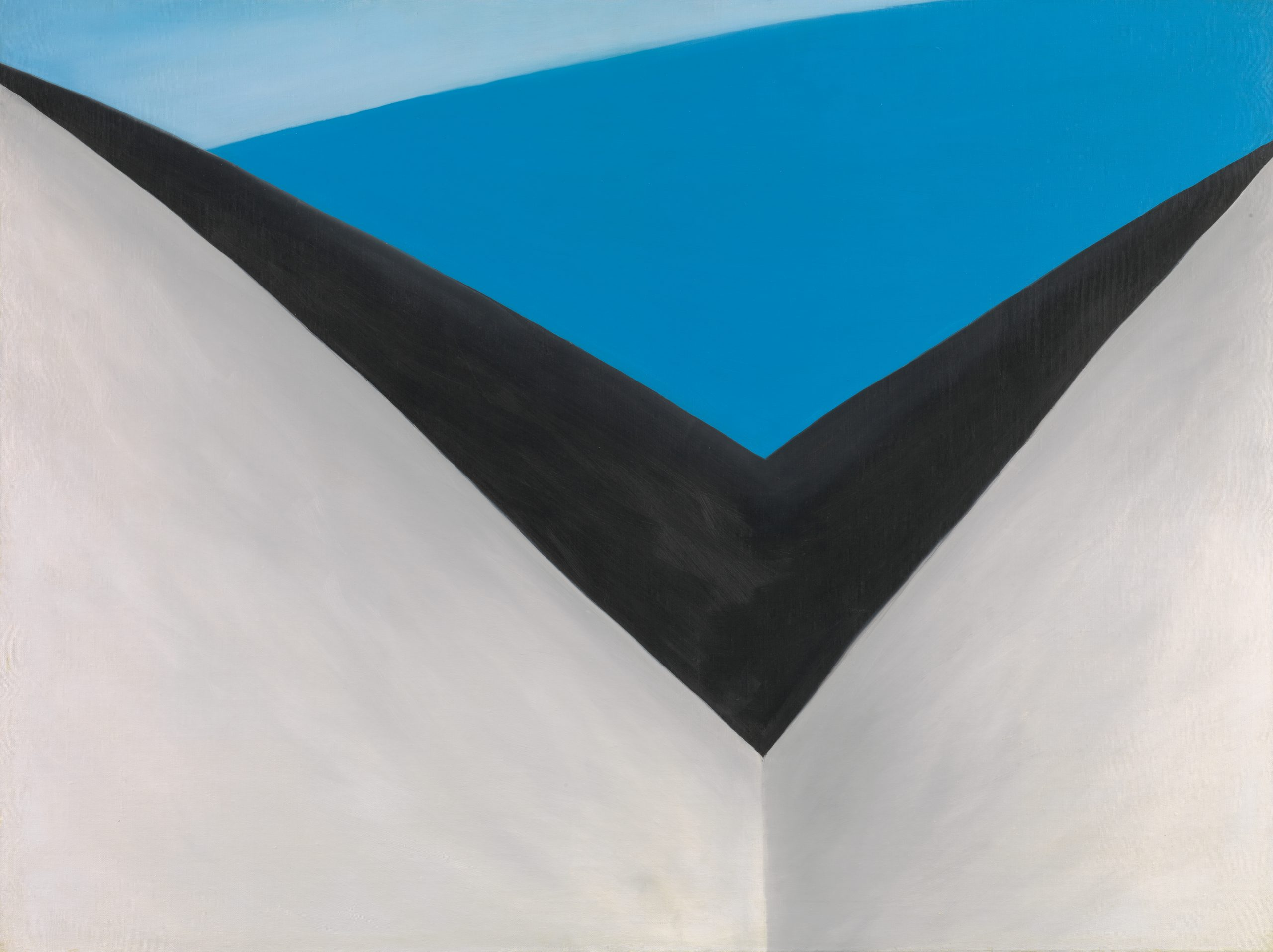 Painted grey and black v-shape structure with a blue sky overhead.
