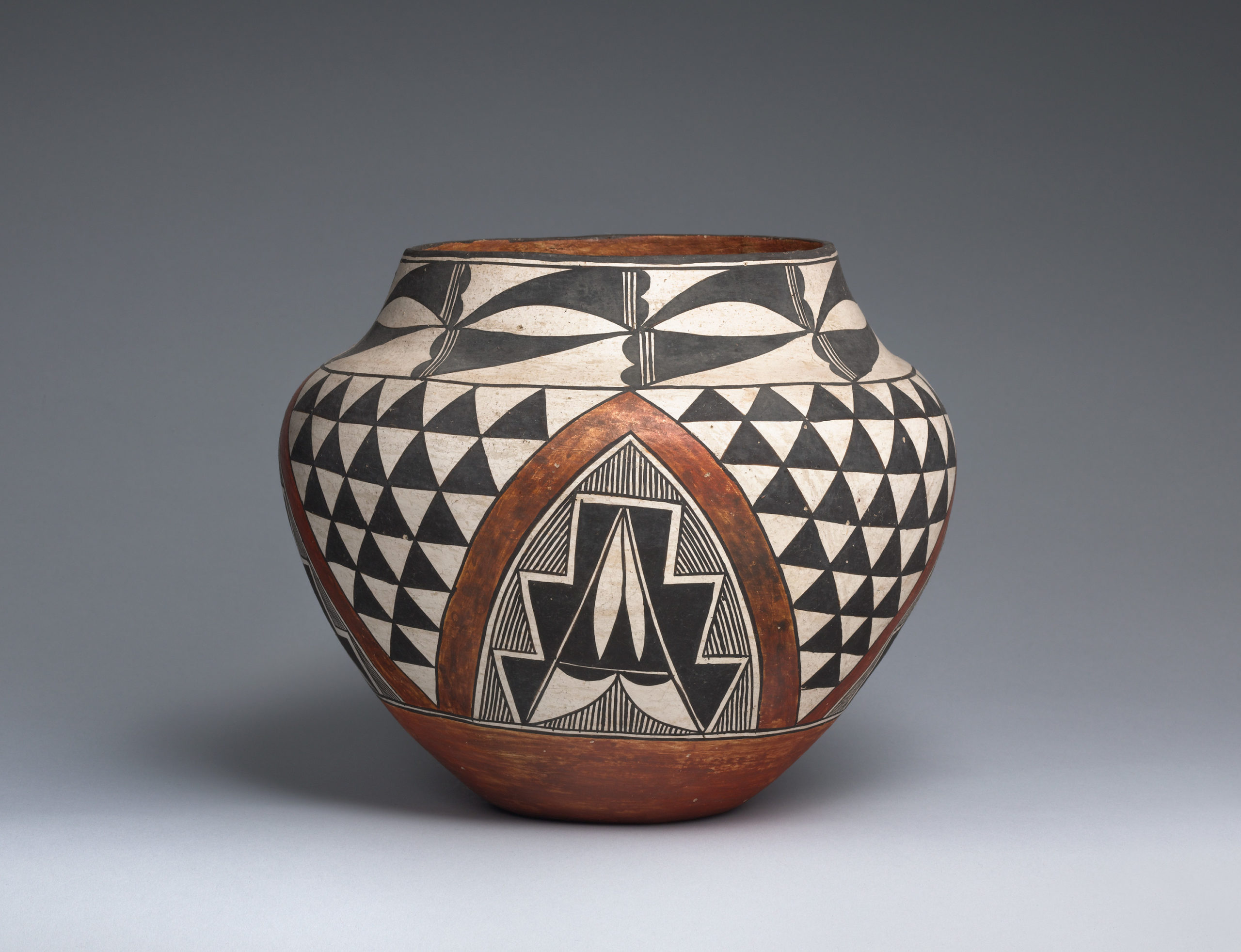 Brown Acoma jar designed with black and white geometric patterns and a centered arch.