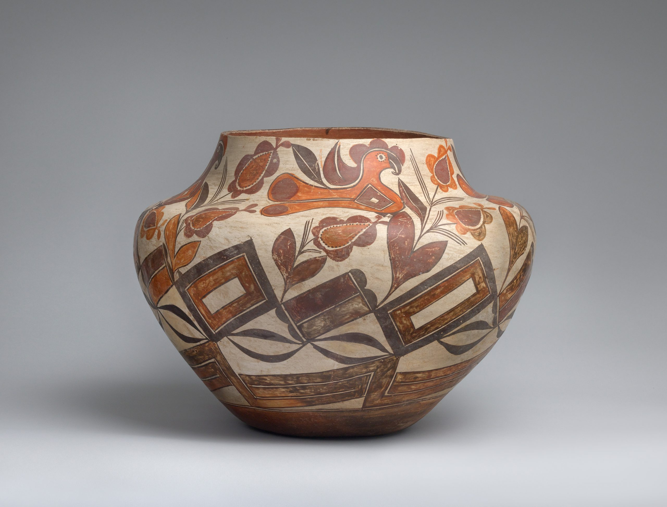 An Acoma jar decorated with birds, flora, and geometric shapes.