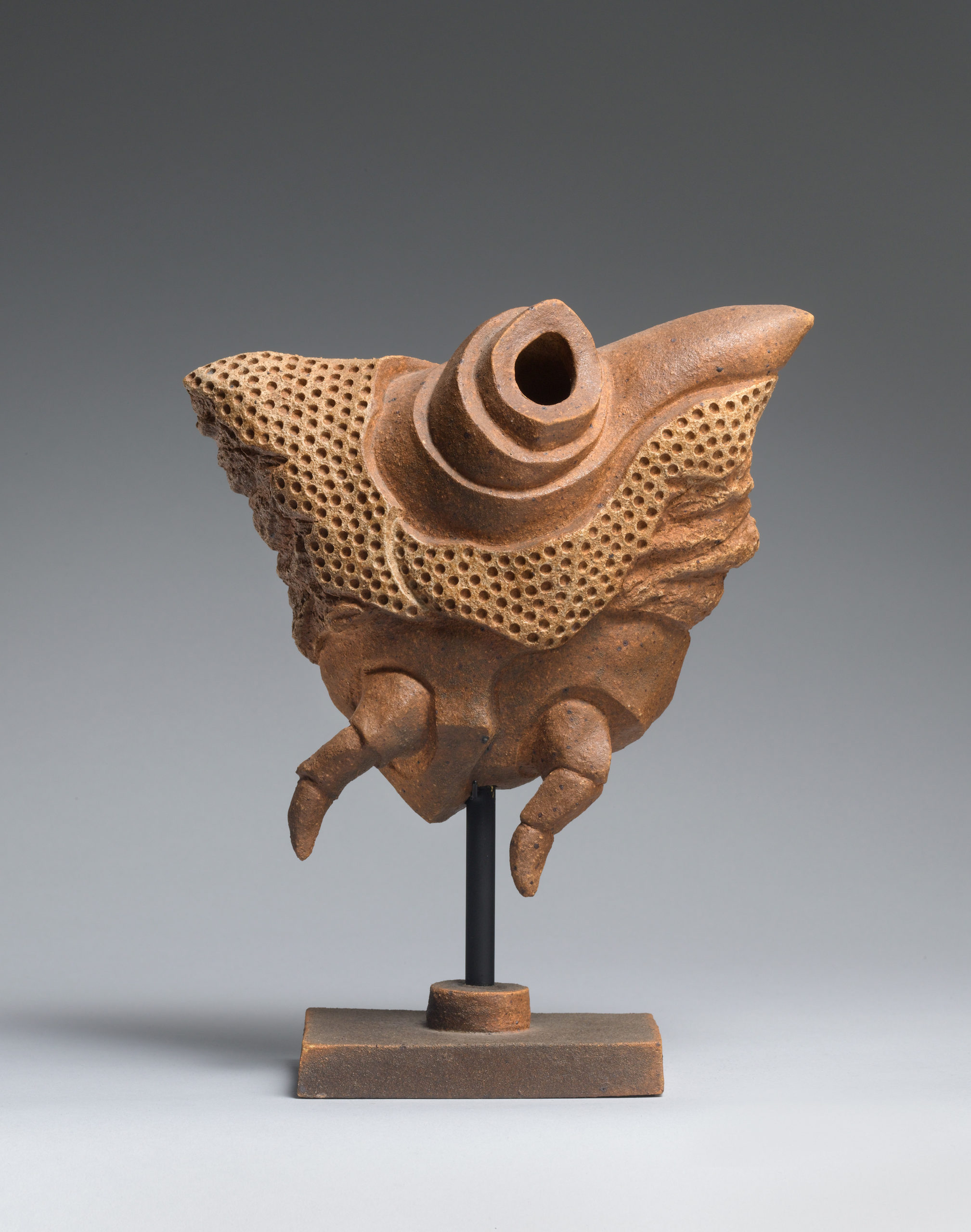 Brown triangular sculpture with mulitple small holes, two smalls legs, and a large hole atop, held up on a short brown pedestal.