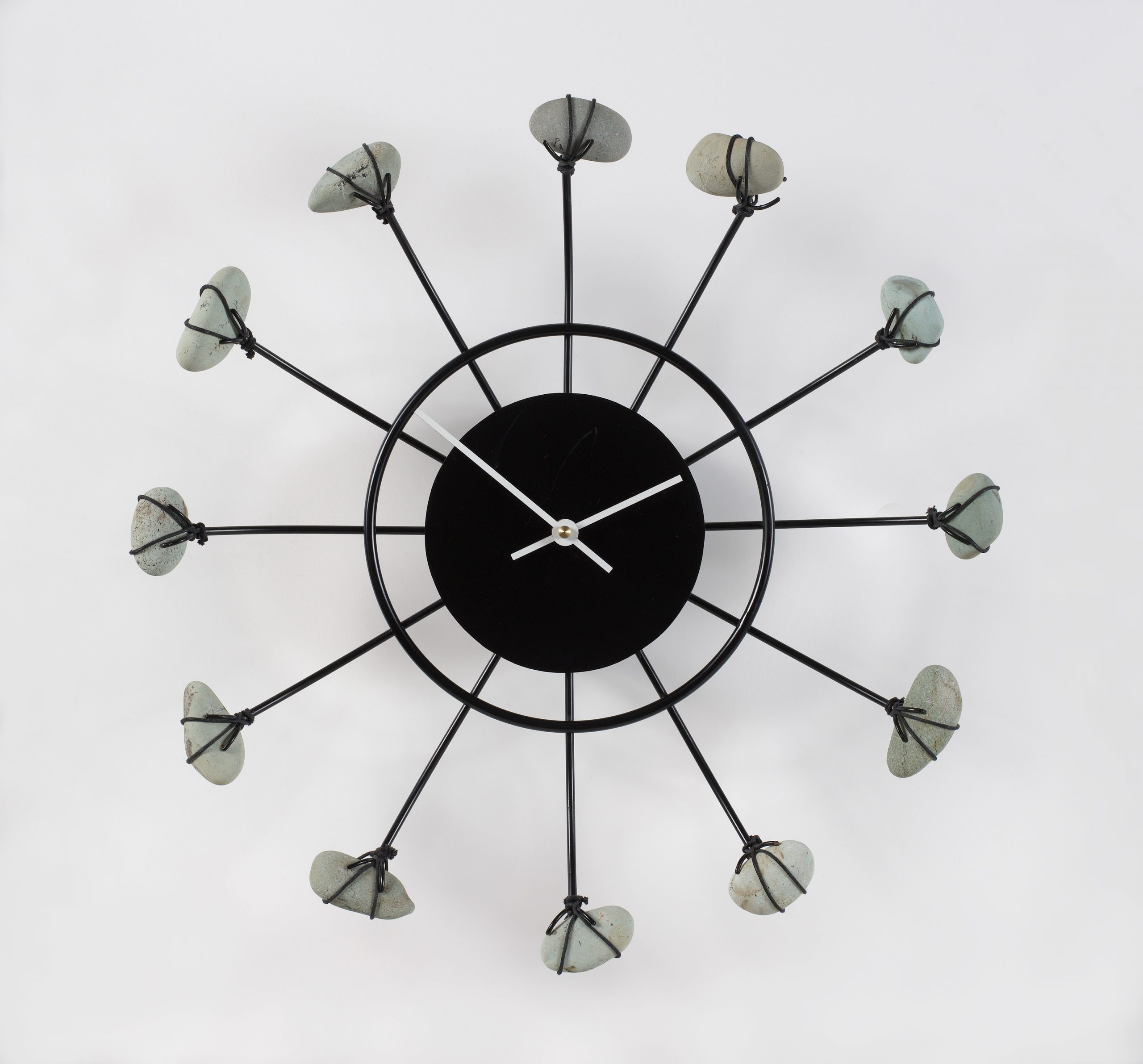 A black metal wall clock with gray stones depicting the hours.