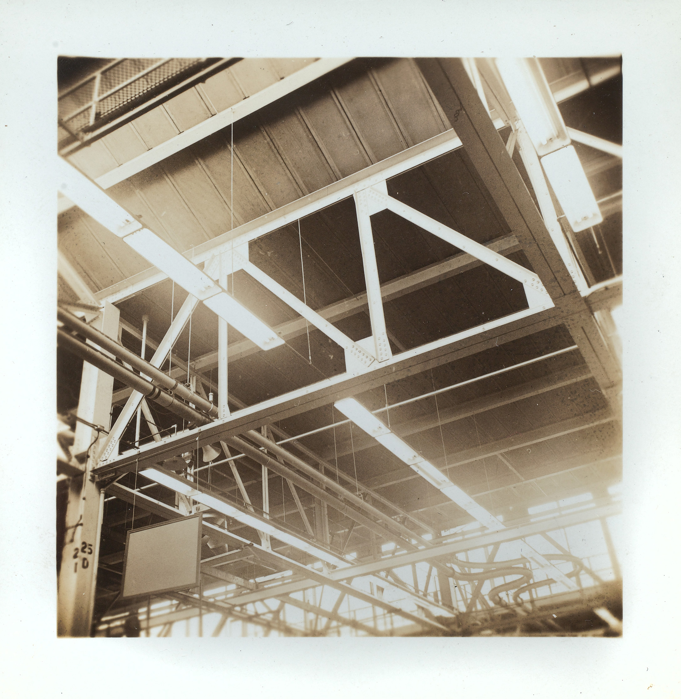 Sepia photograph of the ceiling fixtures in an aircraft plant.