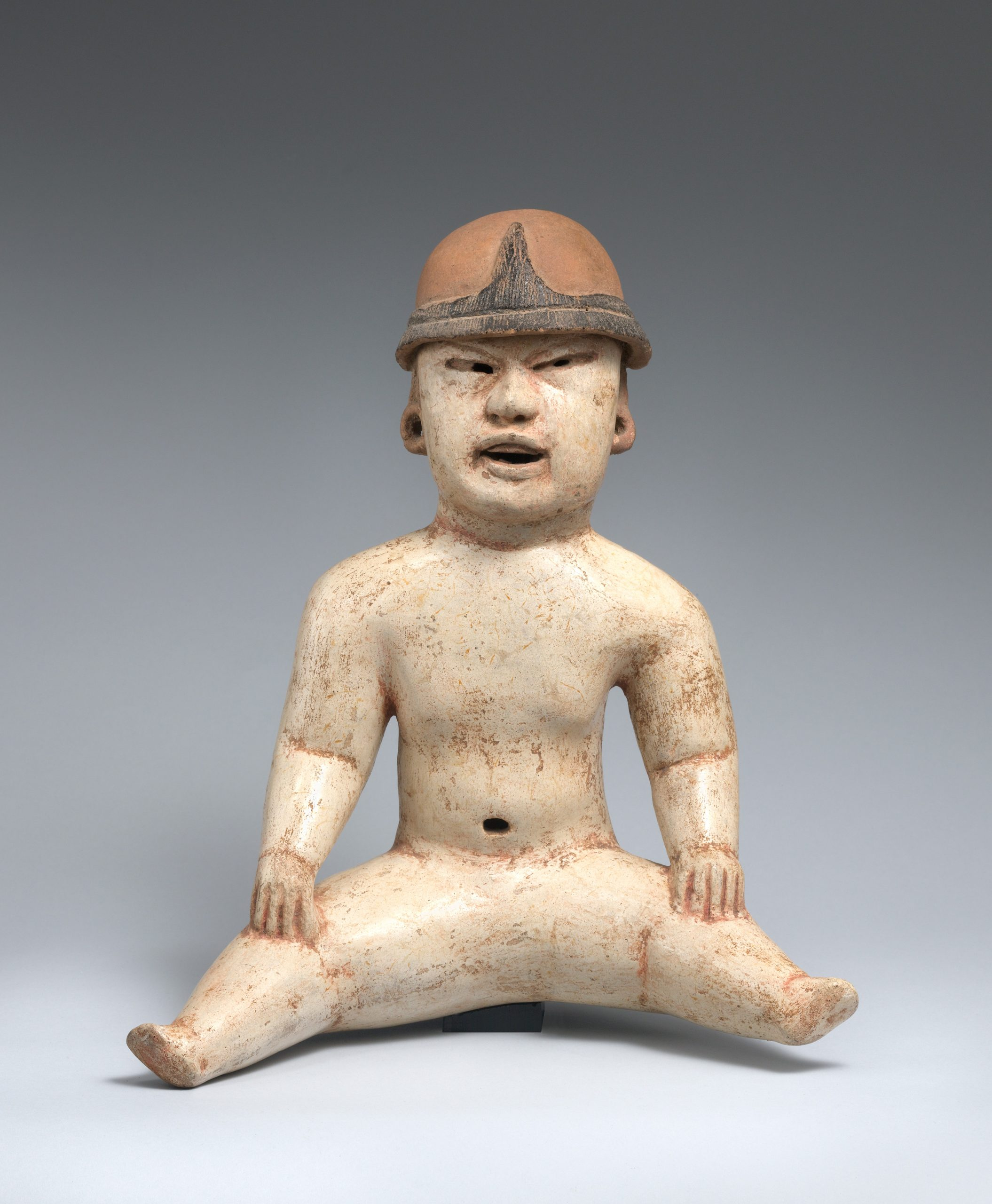 Ceramic seated figure of a baby with a white round body, open mouth, and red head covering.