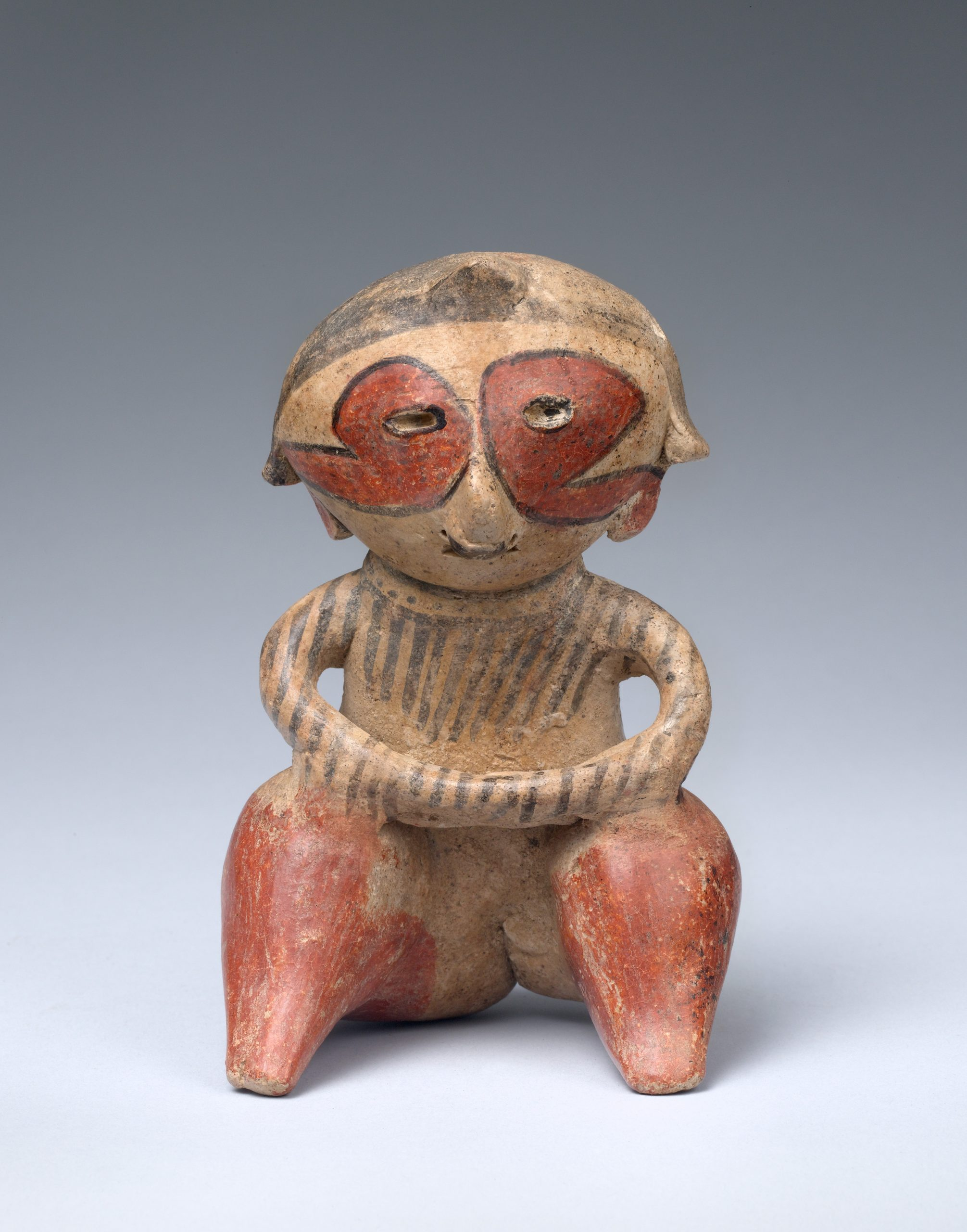 Seated ceramic figure with hands rested on knees, and face and body tattoos in red and black ink.