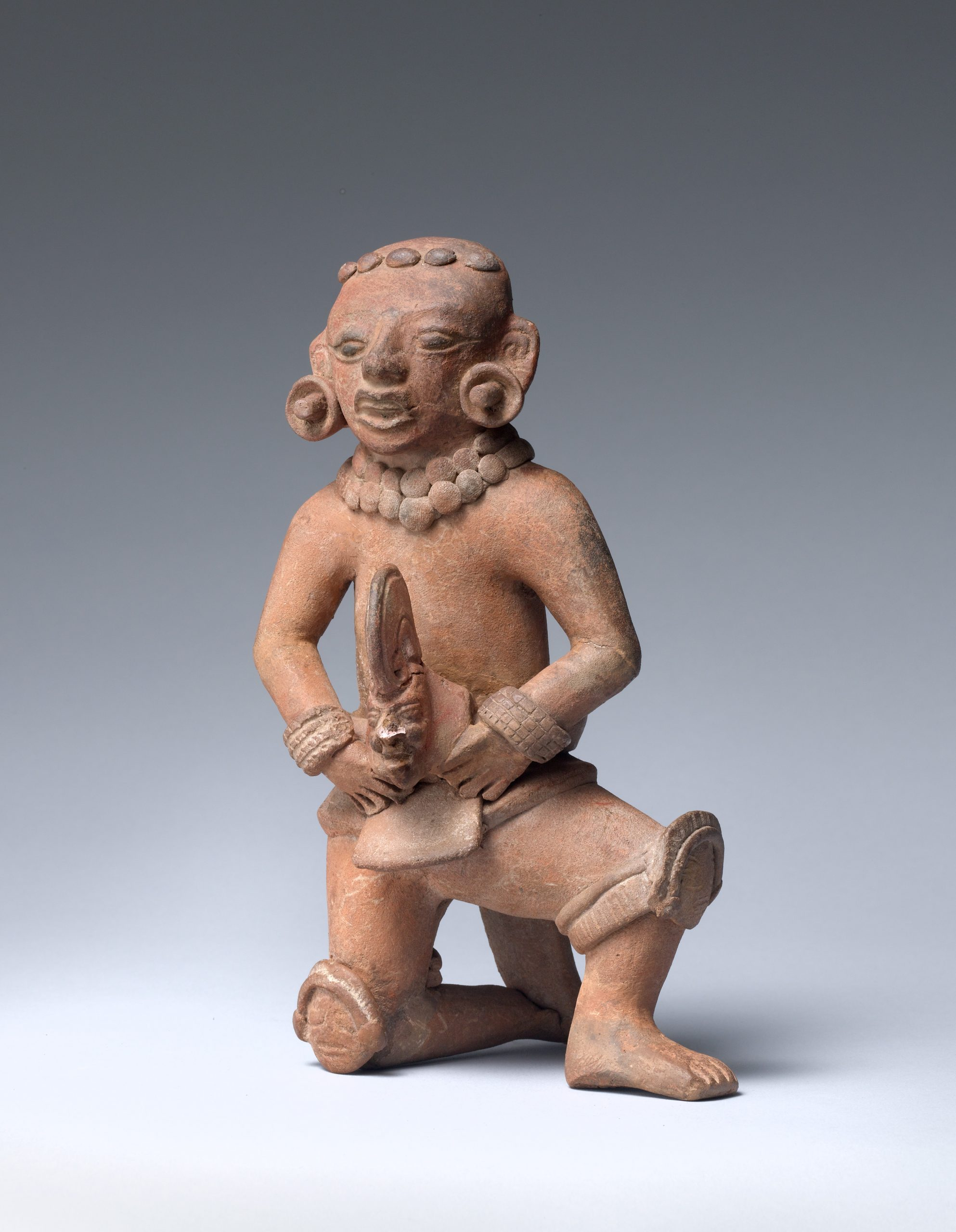 Ceramic sculpture of a ballplayer kneeling on one knee wearing knee pads, hand mitts, and waist pads, and earrings while holding a head.