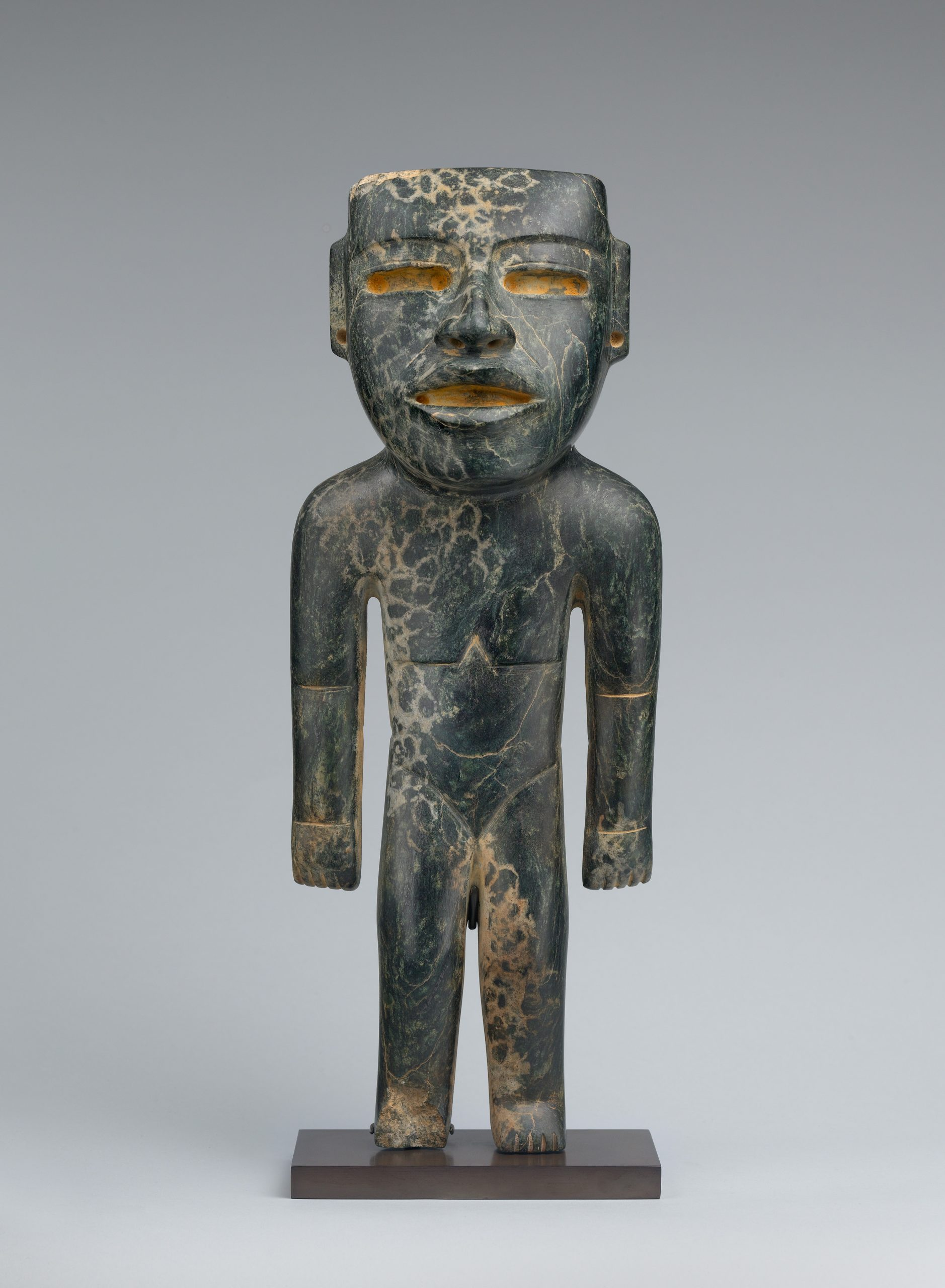 Standing stone figure with a face resembling an Olmec mask with deeply cut eyes and mouth.