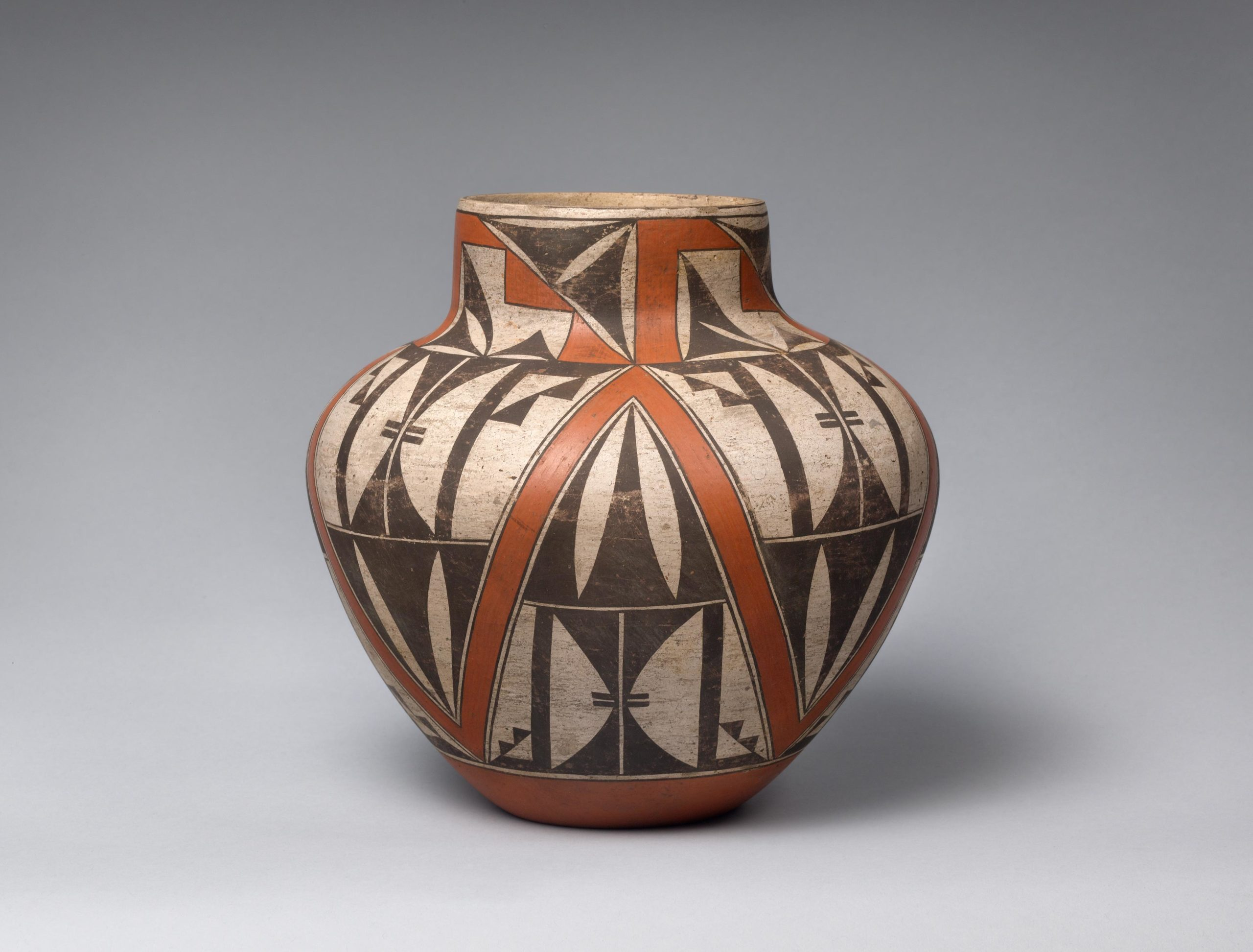 Rust-orange Acoma pot with a black and white geometric design.