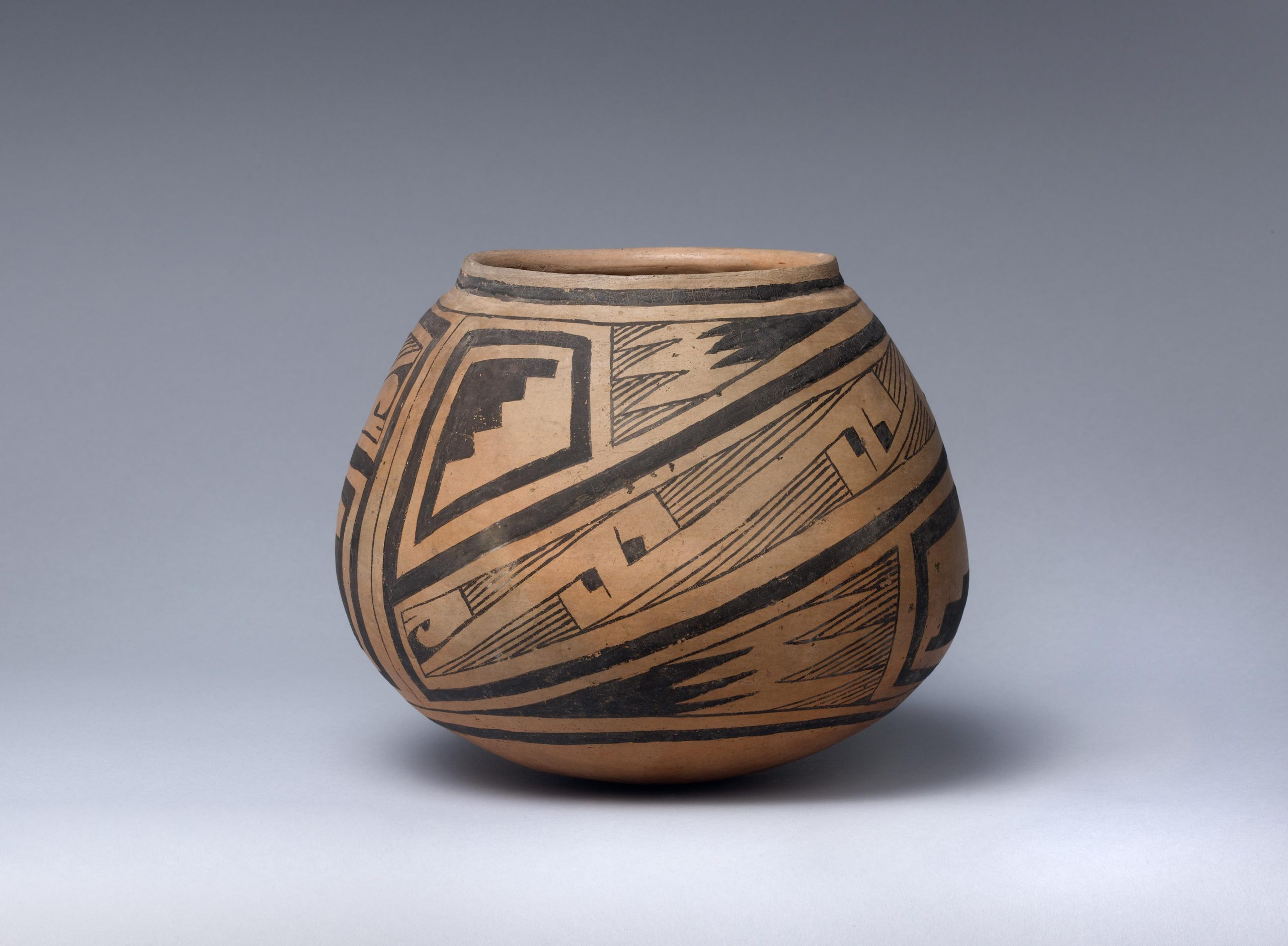 Clay bowl with black geometric design on exterior.