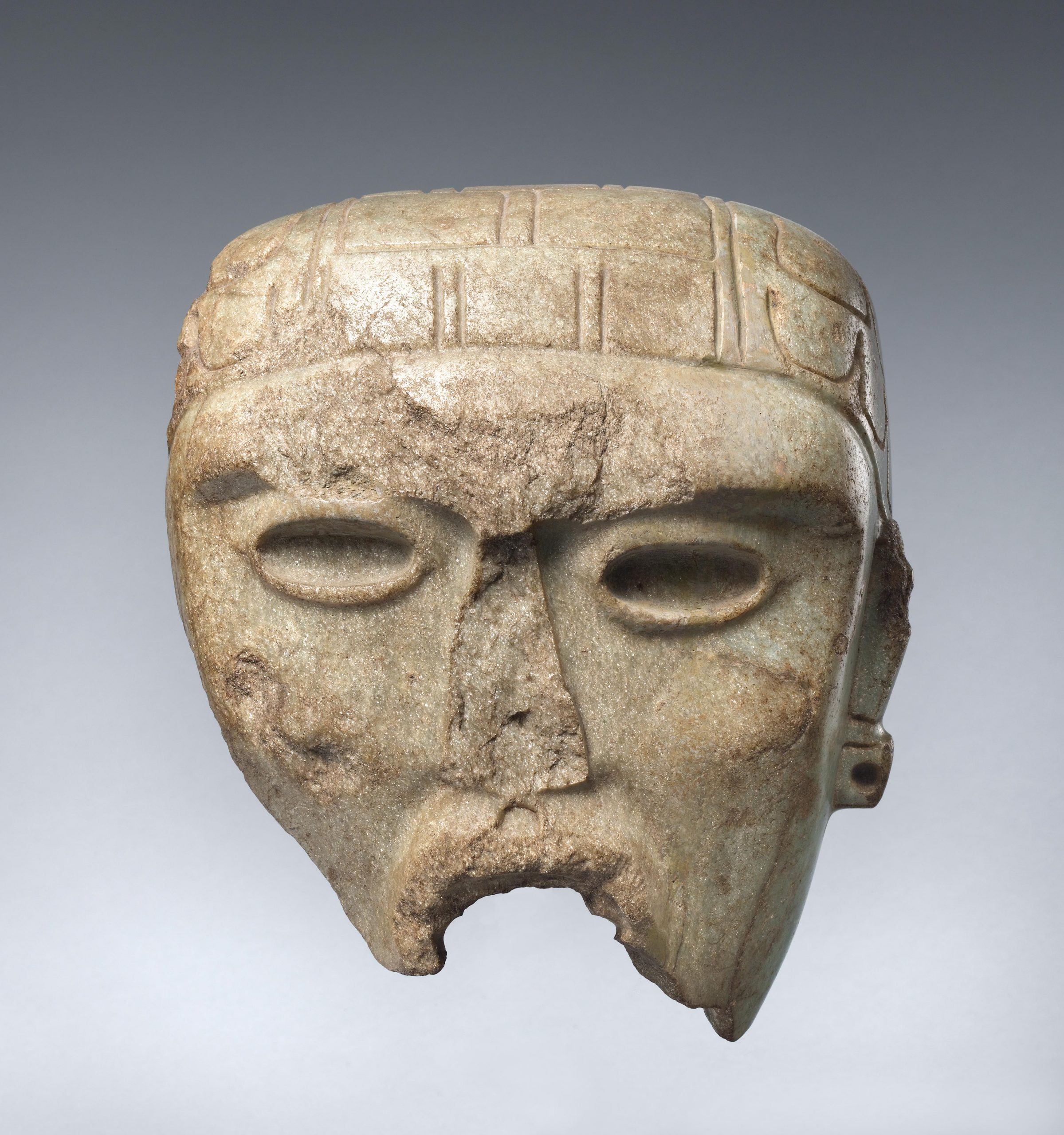 Fragment of a stone mask with hollow eyes and an intricate headdress.