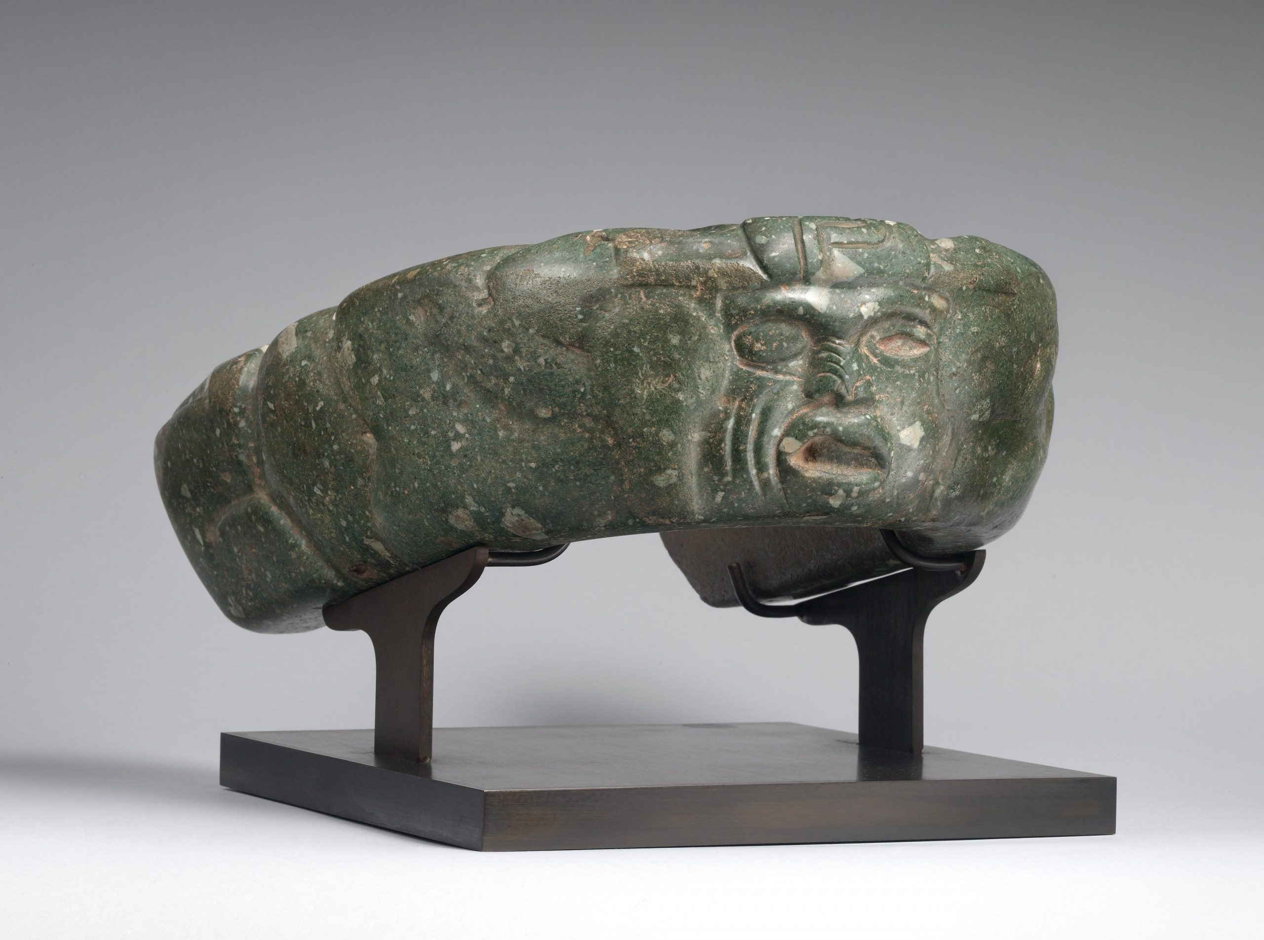 Dark green yoke effigy carved with a human face.