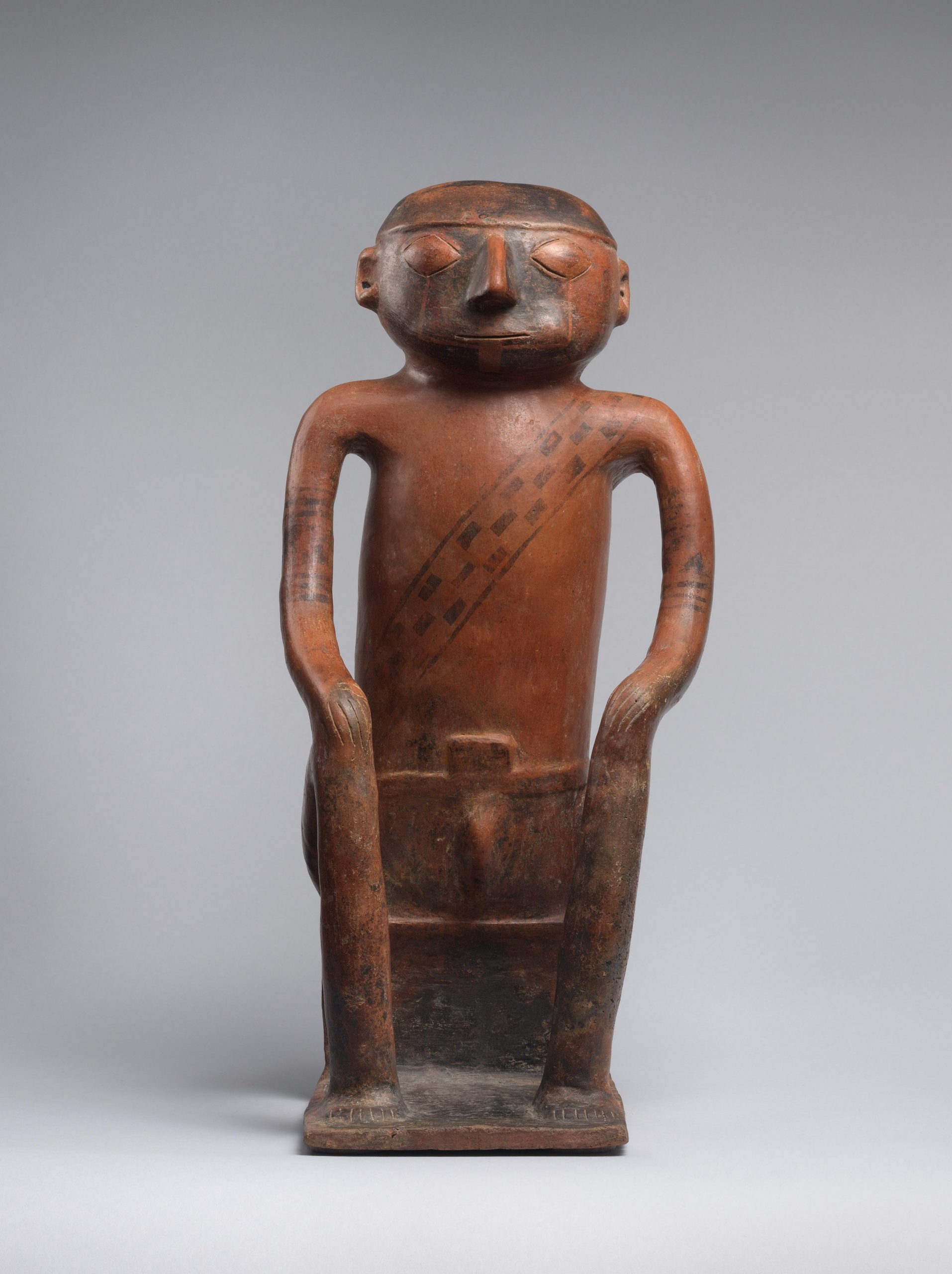 A seated male figure with a painted face, enlarged cheeks, and a woven band across the chest.