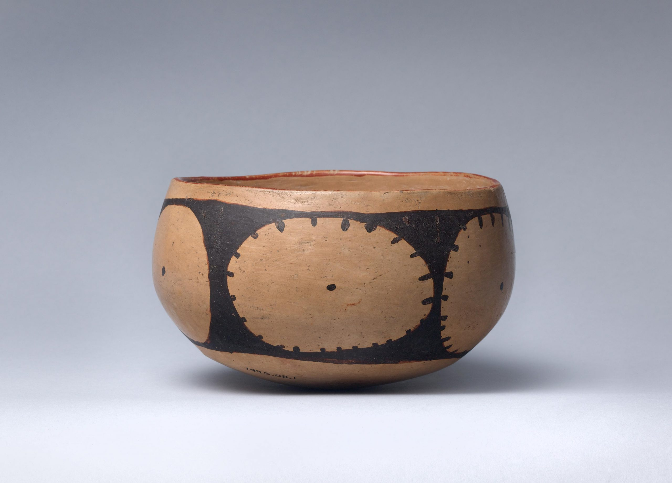Decorative ceramic bowl covered with complex, interlocking geometrical designs with two abstract rabbit heads on either side.
