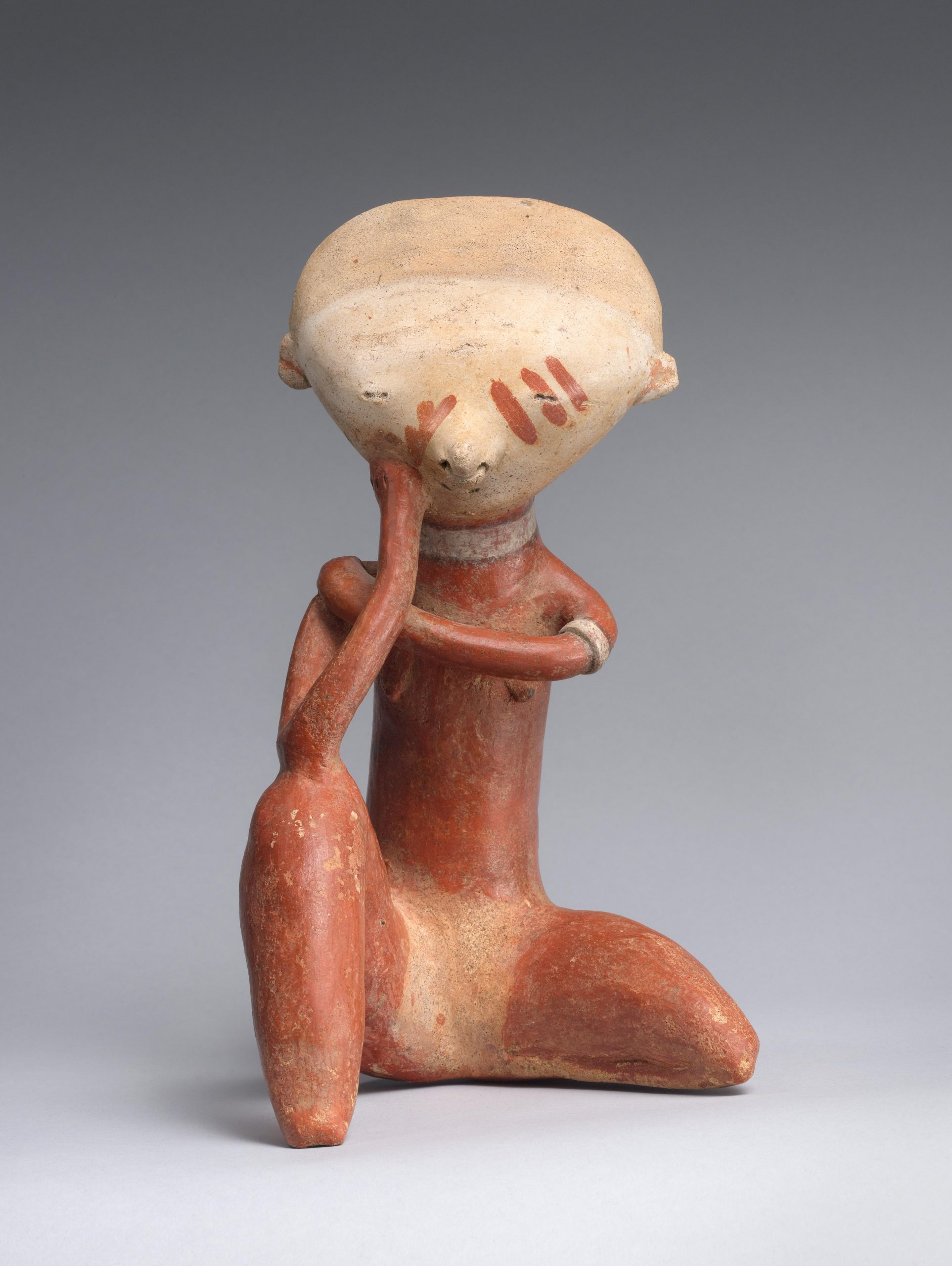 A stylized ceramic figure with a red body and beige head, red face paint, and a hand resting on its face.