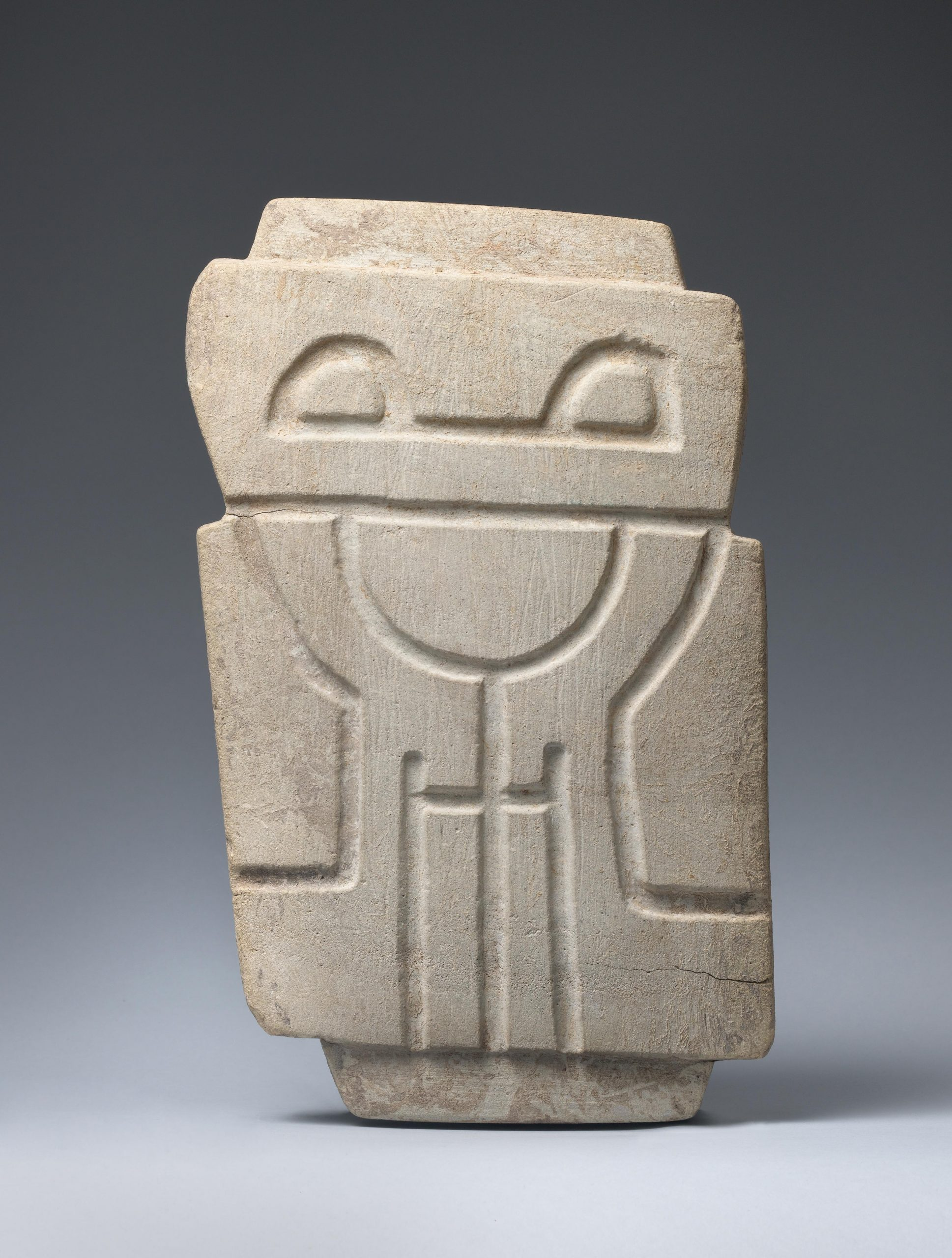 Abstract stone sculpture of a standing figure with indentations indicating facial features and arms at torso.