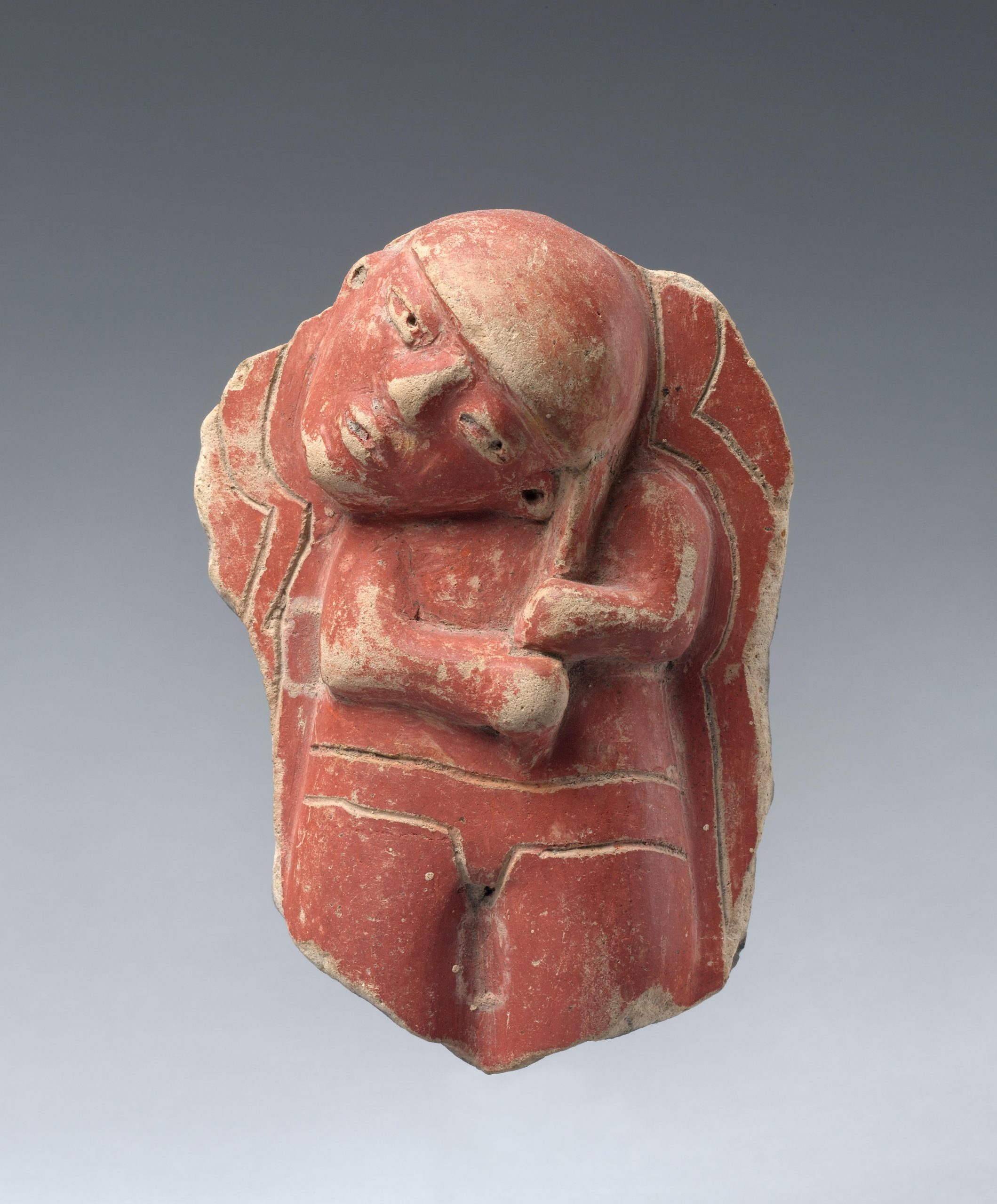 Ceramic fragment of a figure with a tilted head, painted in red.