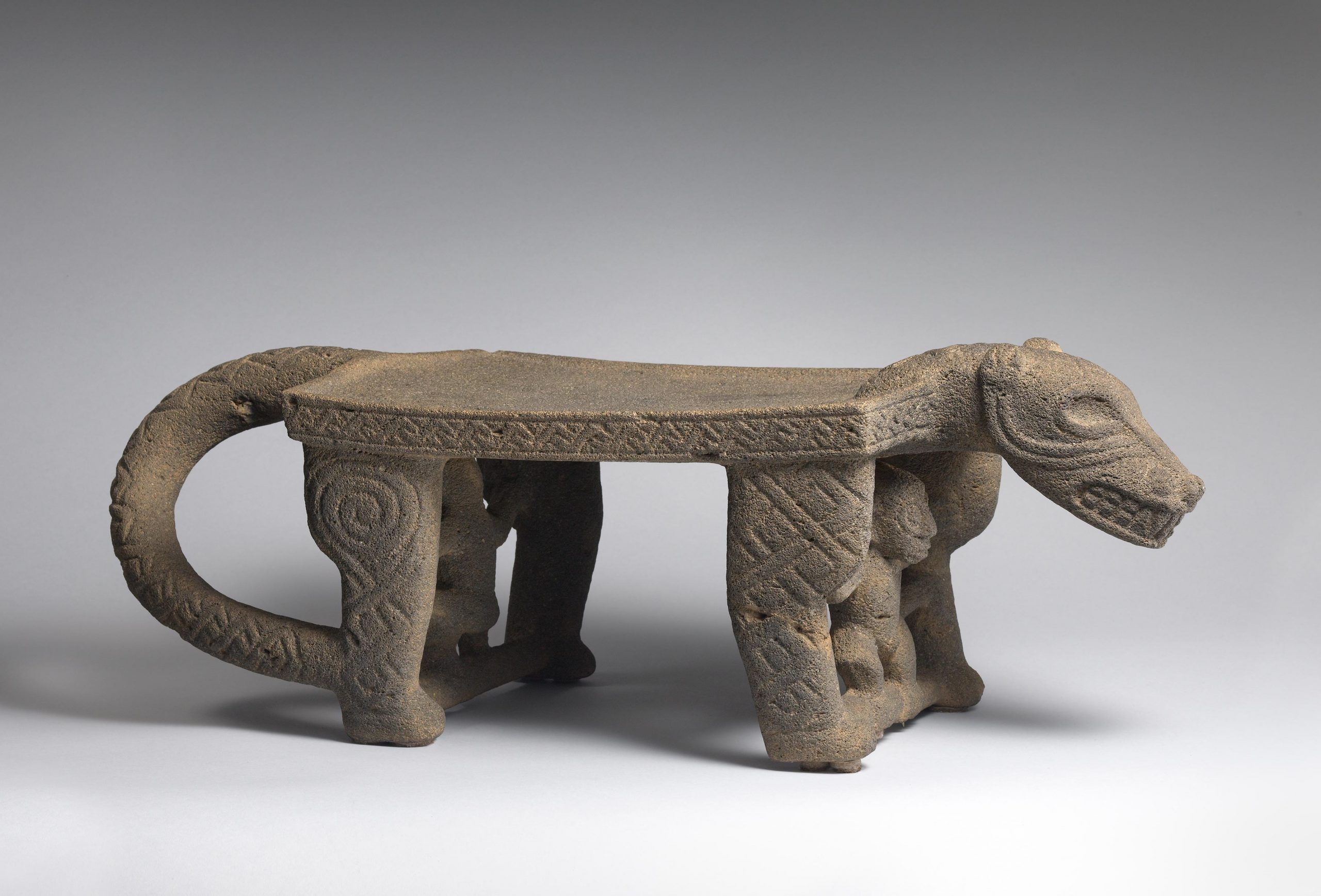 Stone metate carved in the shape of a jaguar with monkeys between its legs.
