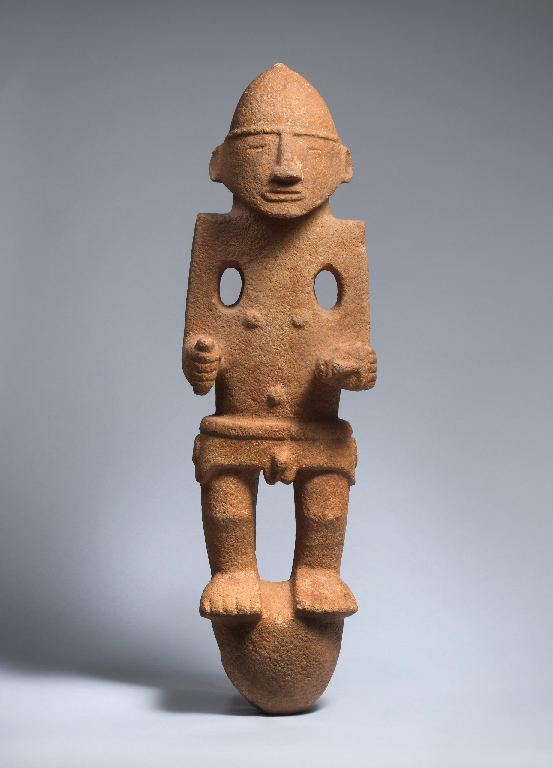 Stone sculpture of a man holding a small head and a tool, wearing a helmet and a belt.