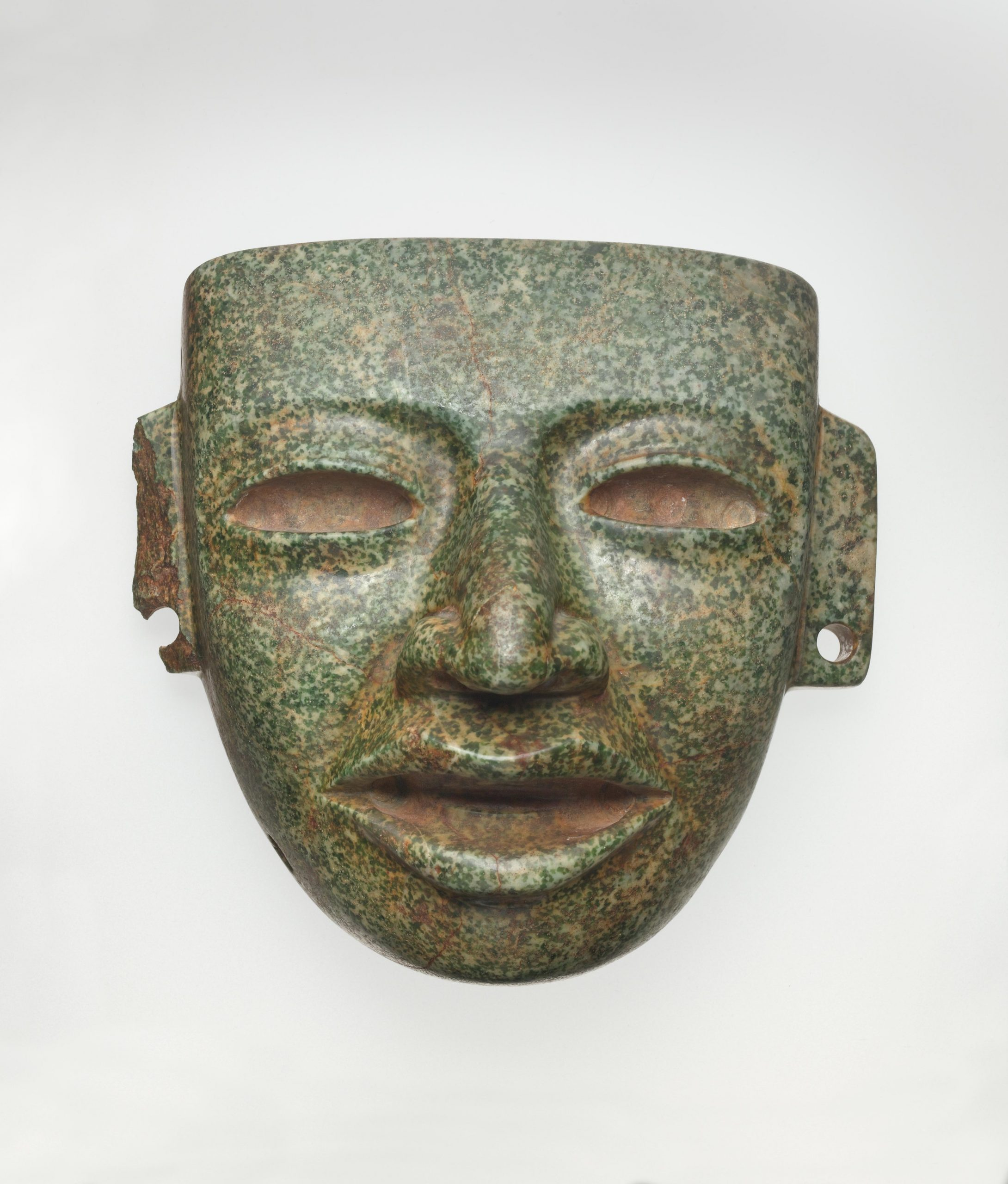Mottled green stone face mask with open mouth, hollowed eyes, and pierced ears.