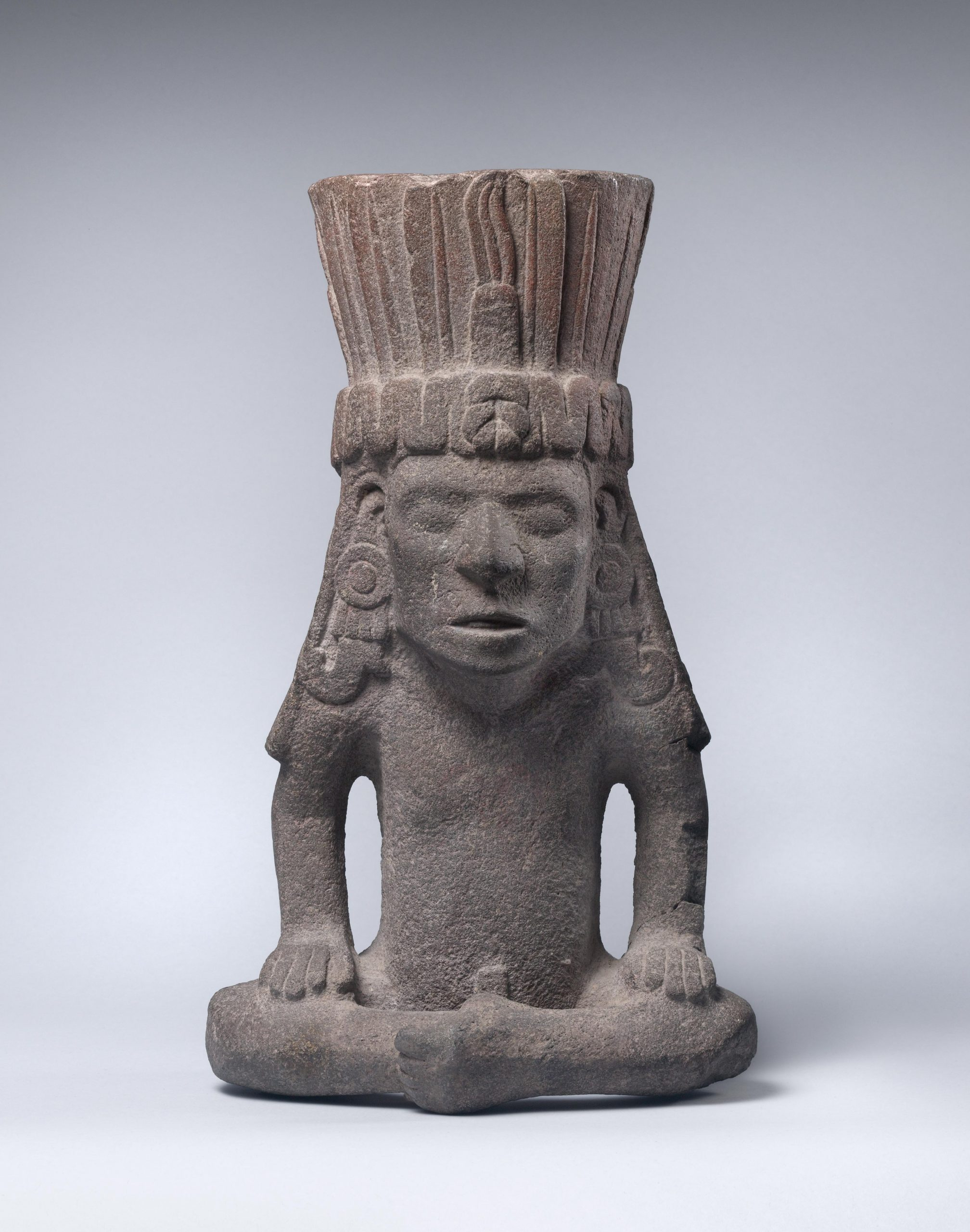 Sculpture of a man seated with crossed legs and wearing a large headdress and long, intricate earings; his mouth is open as if he is in mid-speech.