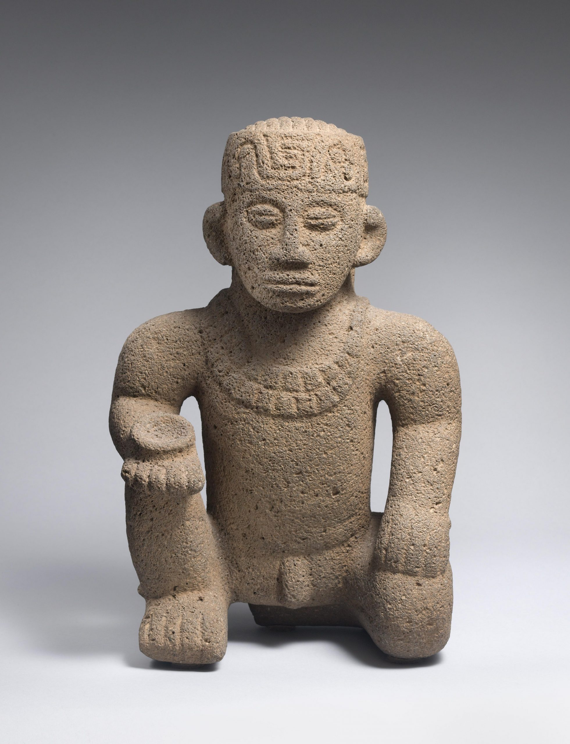 Stone sculpture of man kneeling on one knee, holding a small dish, wearing a beaded necklace and headdress.