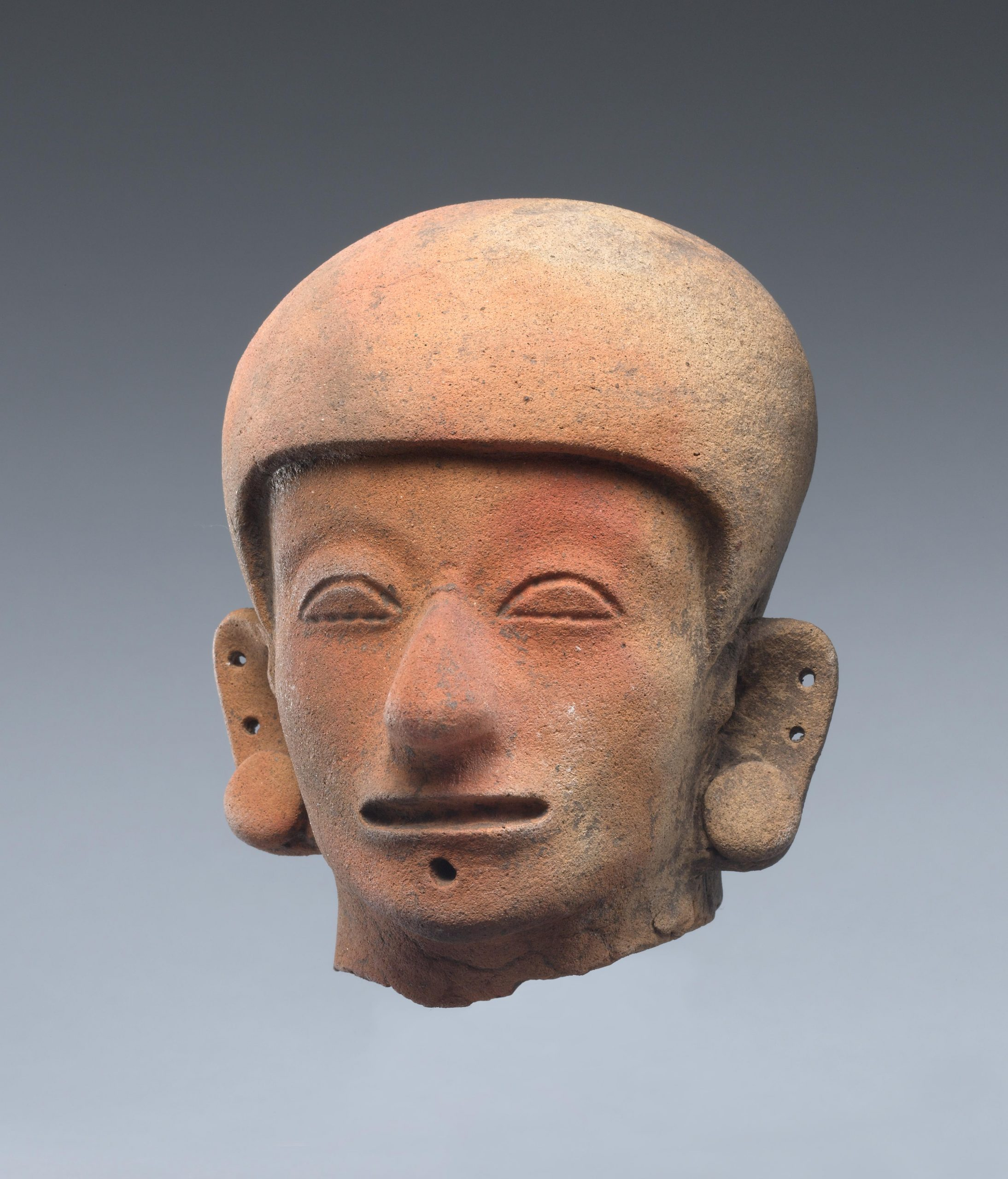 Ceramic human head wearing a helmet and ear spools.