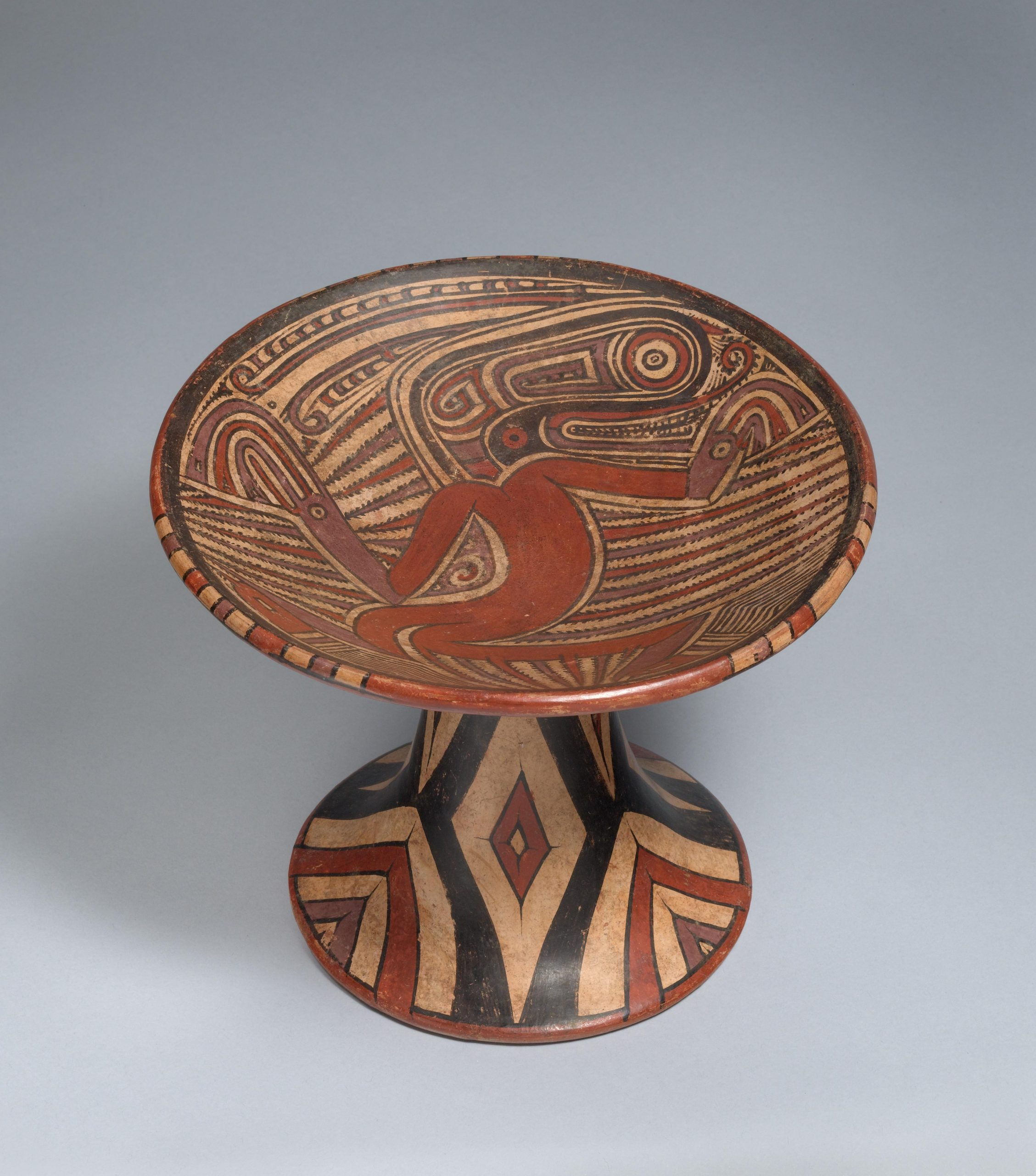 Pedestal plate with human and crocodile figures surrounded by patterns with geometric designs the on the base.