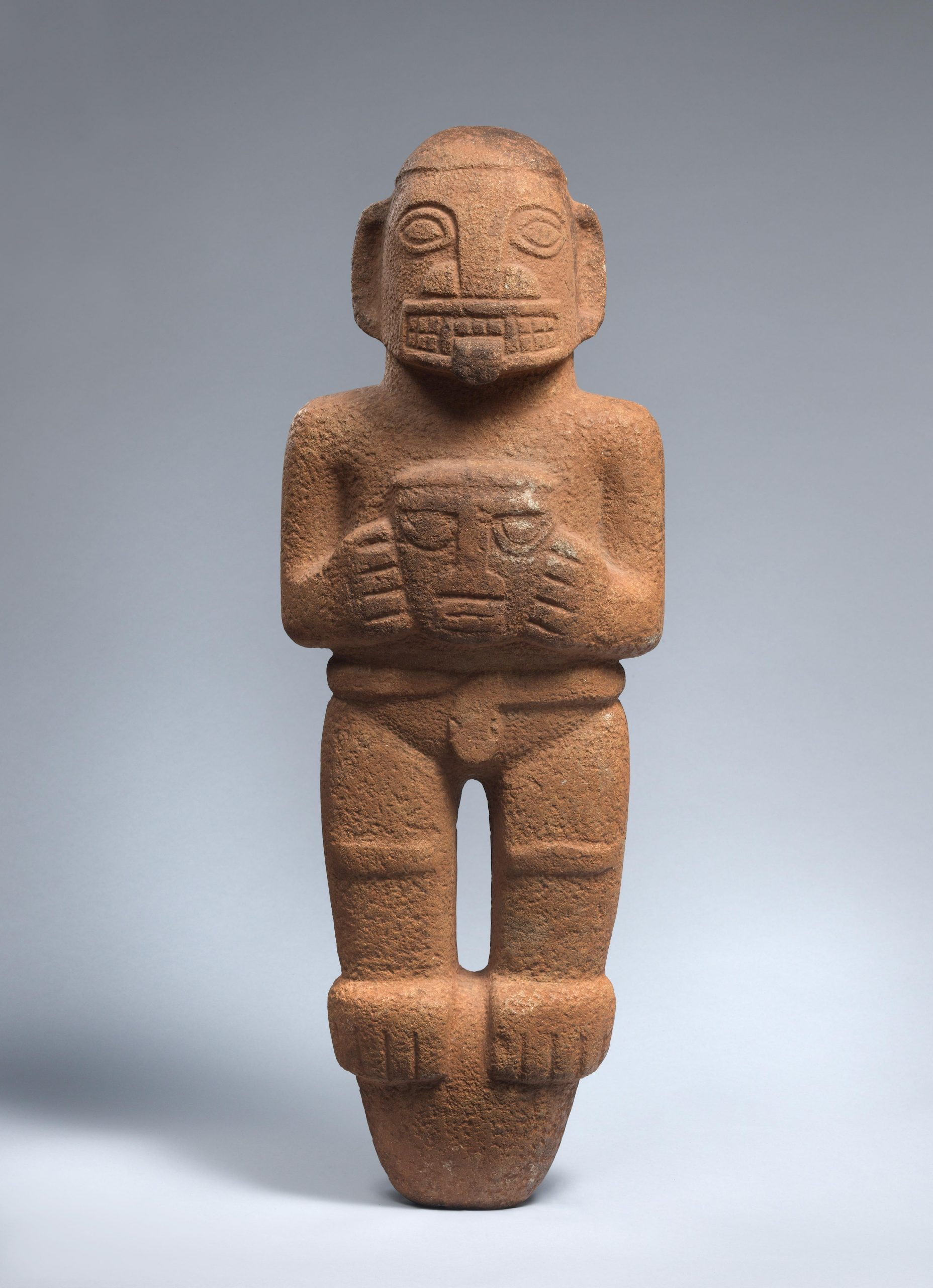 Stylized human figure carved into grey-green stone.