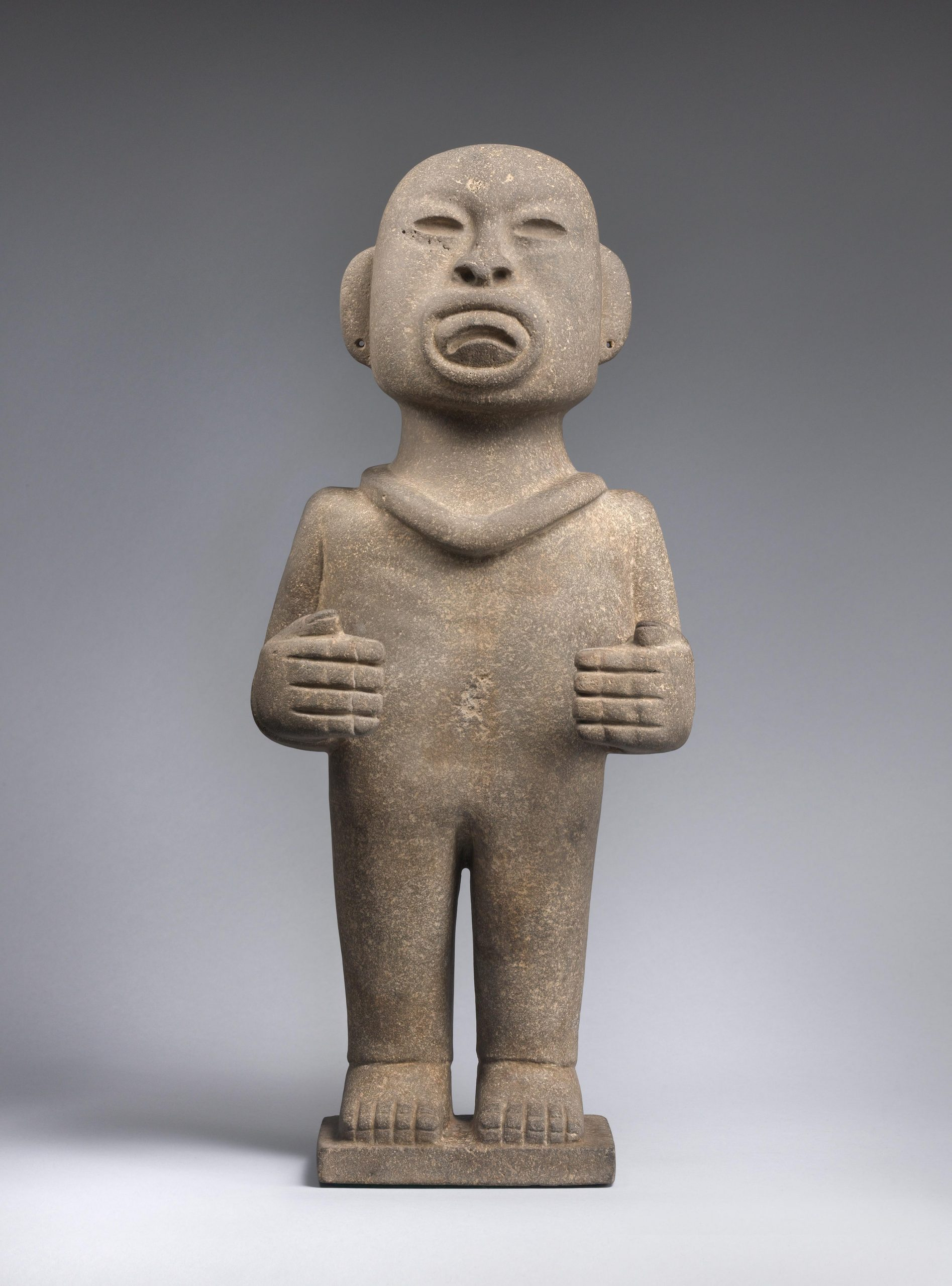 Gray standing stone figure with indented eyes and mouth, pierced ears, a bald head, and bent arms.