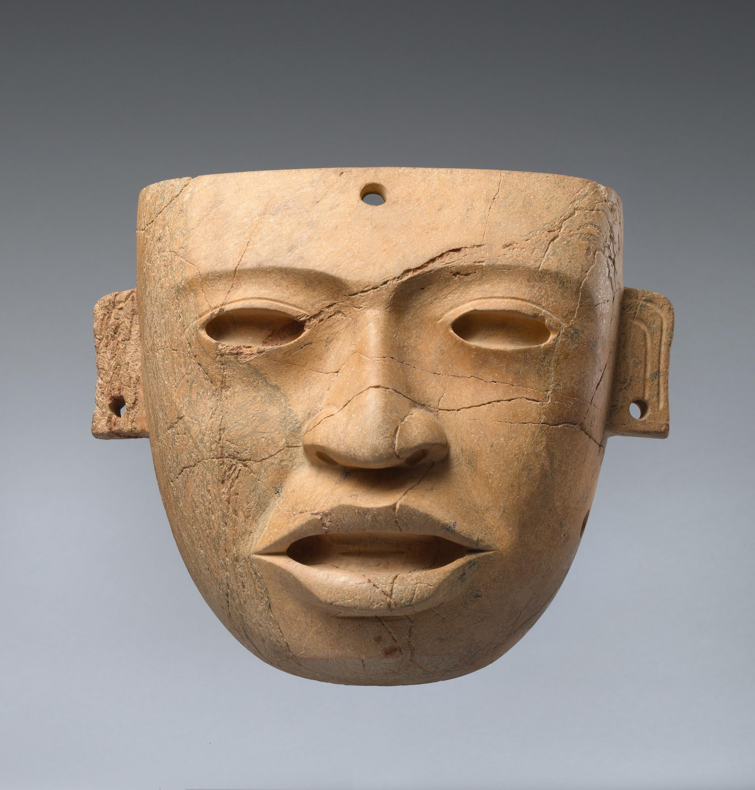 Light brown realistic face mask with hollowed eyes, open mouth, and pierced ears.
