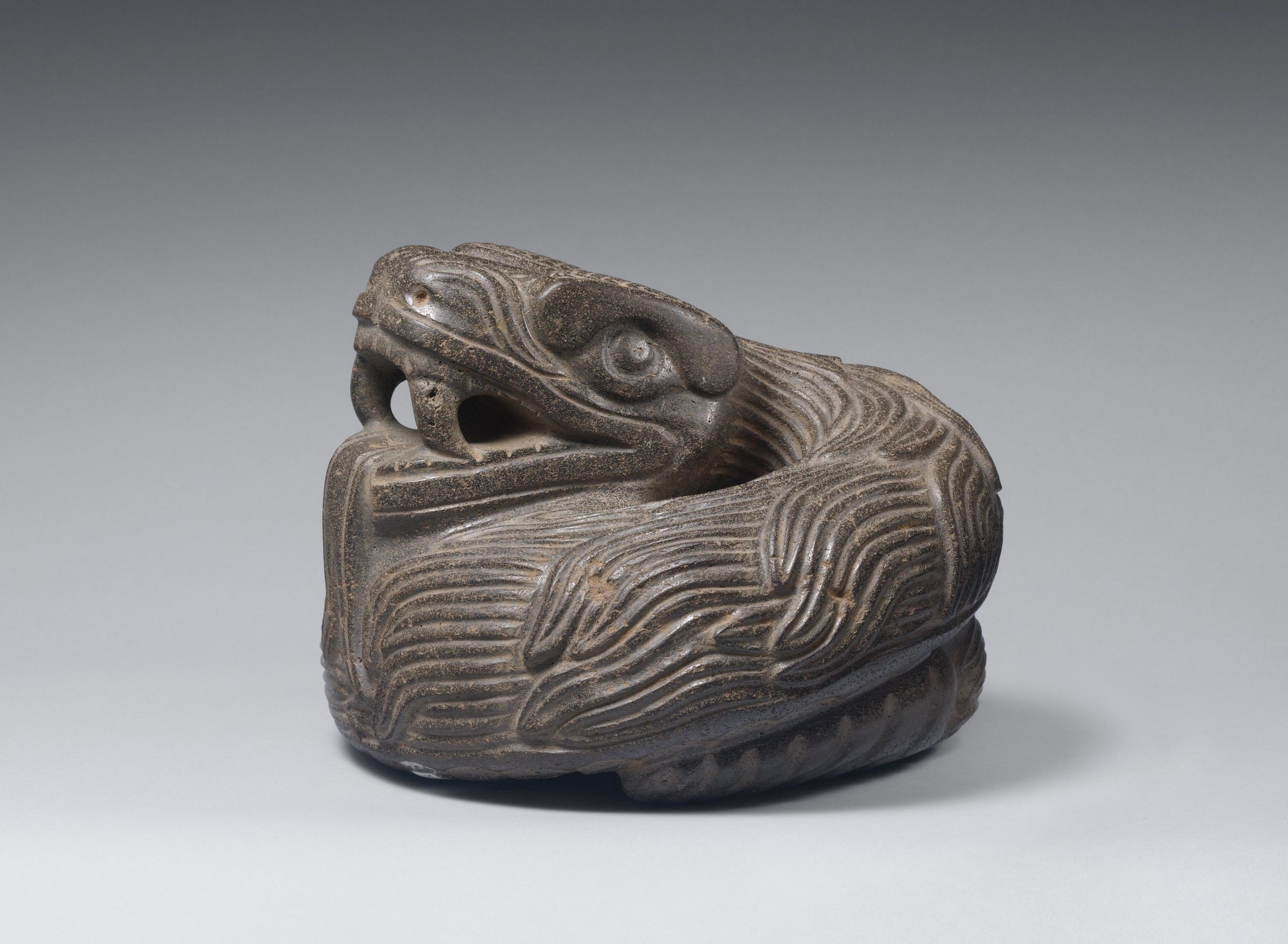 Sculpture of a coiled quetzalcoatl feathered serpent with open mouth exposing prominent fangs.
